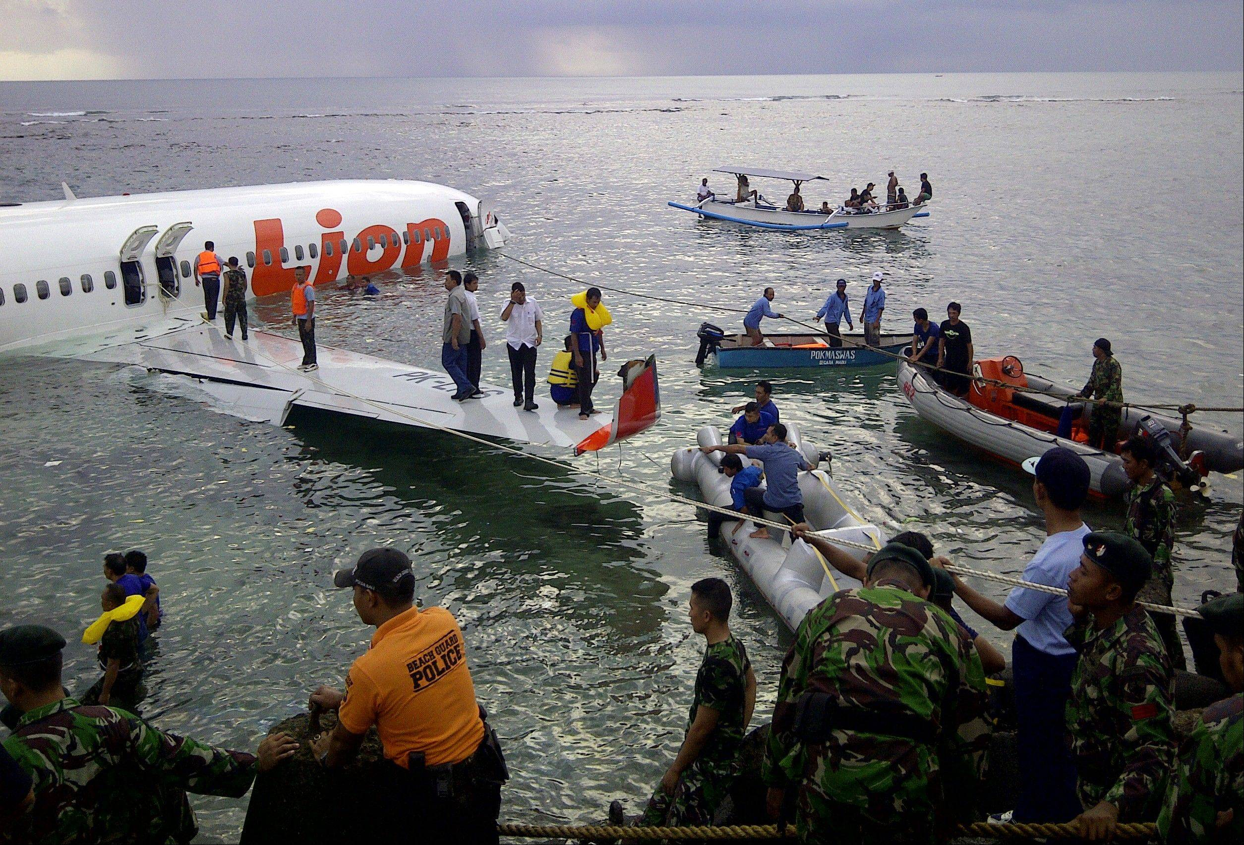 Rescuers assist evacuating passengers at the crash site of a Lion Air plane in Bali, Indonesia, on Saturday. The plane carrying more than 100 passengers and crew overshot a runway on the Indonesian resort island of Bali on Saturday and crashed into the sea, injuring nearly two dozen people, officials said.