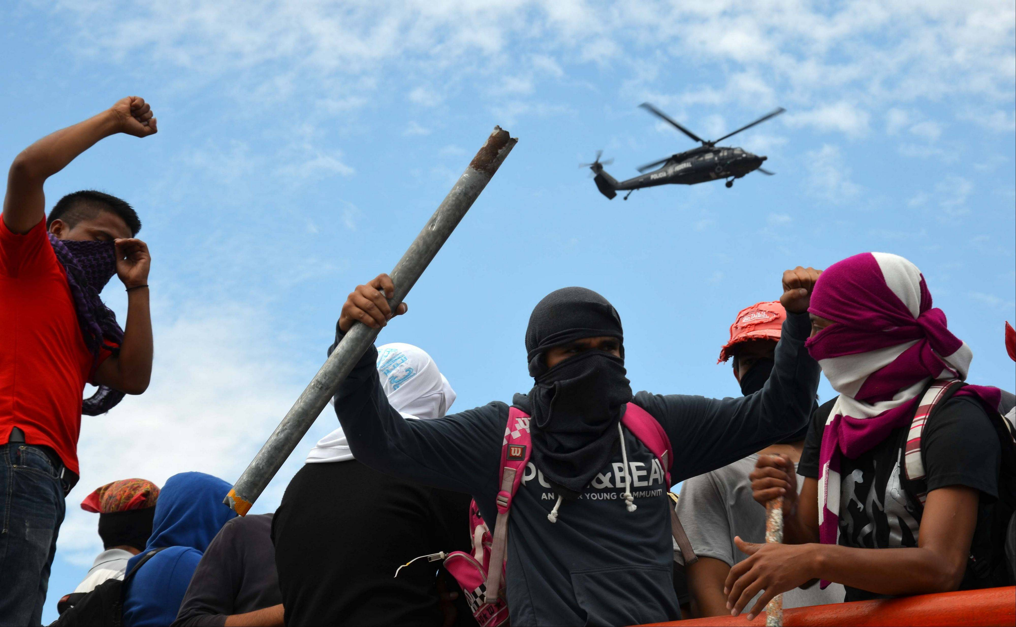 Young teachers block a major highway as they chant slogans, one holding a metal pipe, as a federal police helicopter flies overhead in Chilpancingo, Mexico, Thursday. The teachers, who are protesting an educational reform that will submit them to evaluation and loosen union control over hiring and firing, left peacefully after negotiating with police.