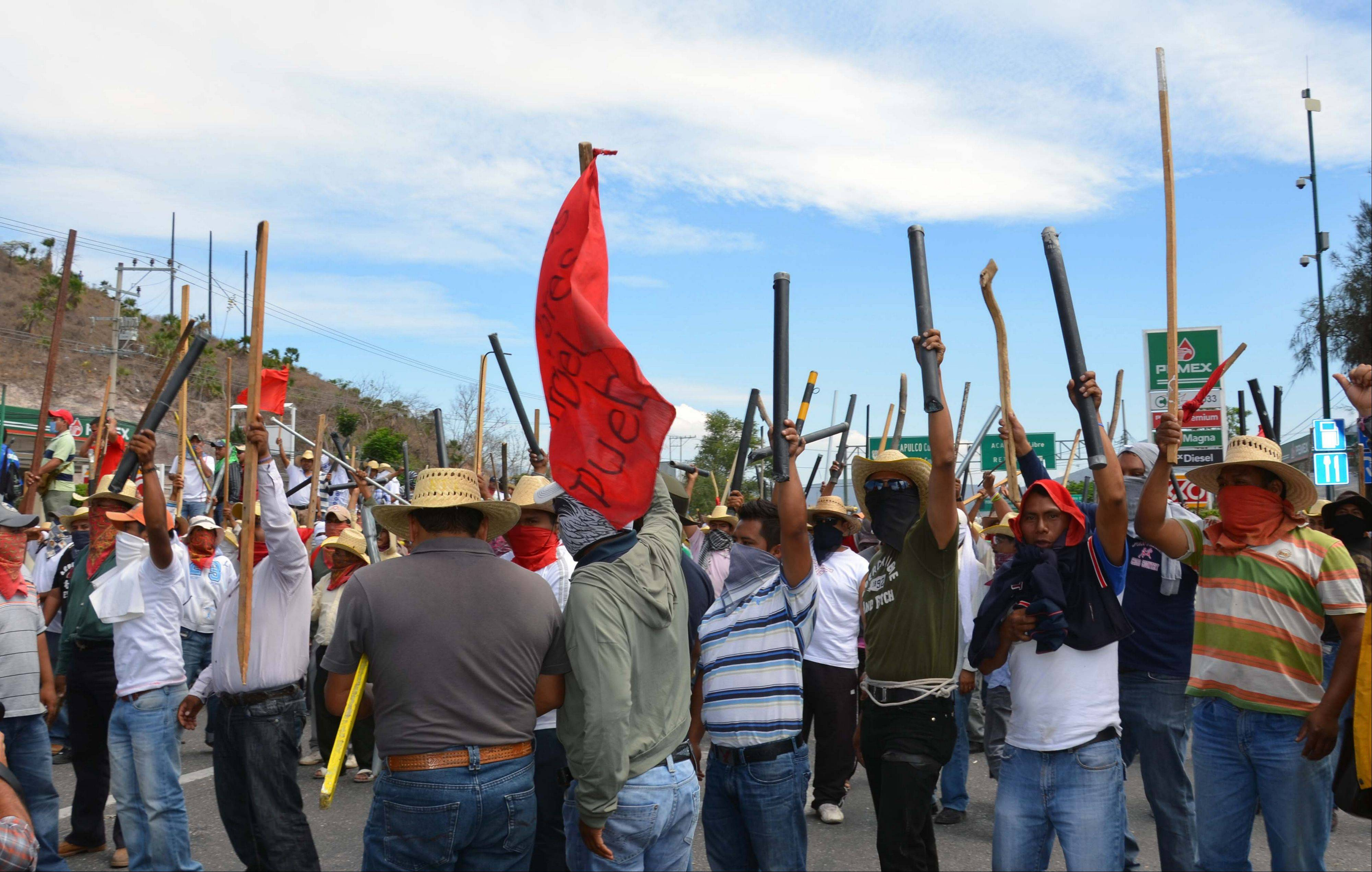 Teachers chant slogans holding up metal pipes and wooden sticks while blocking a major highway in Chilpancingo, Mexico, Thursday. The teachers, who are protesting an educational reform that will submit them to evaluation and loosen union control over hiring and firing, left peacefully after negotiating with police.