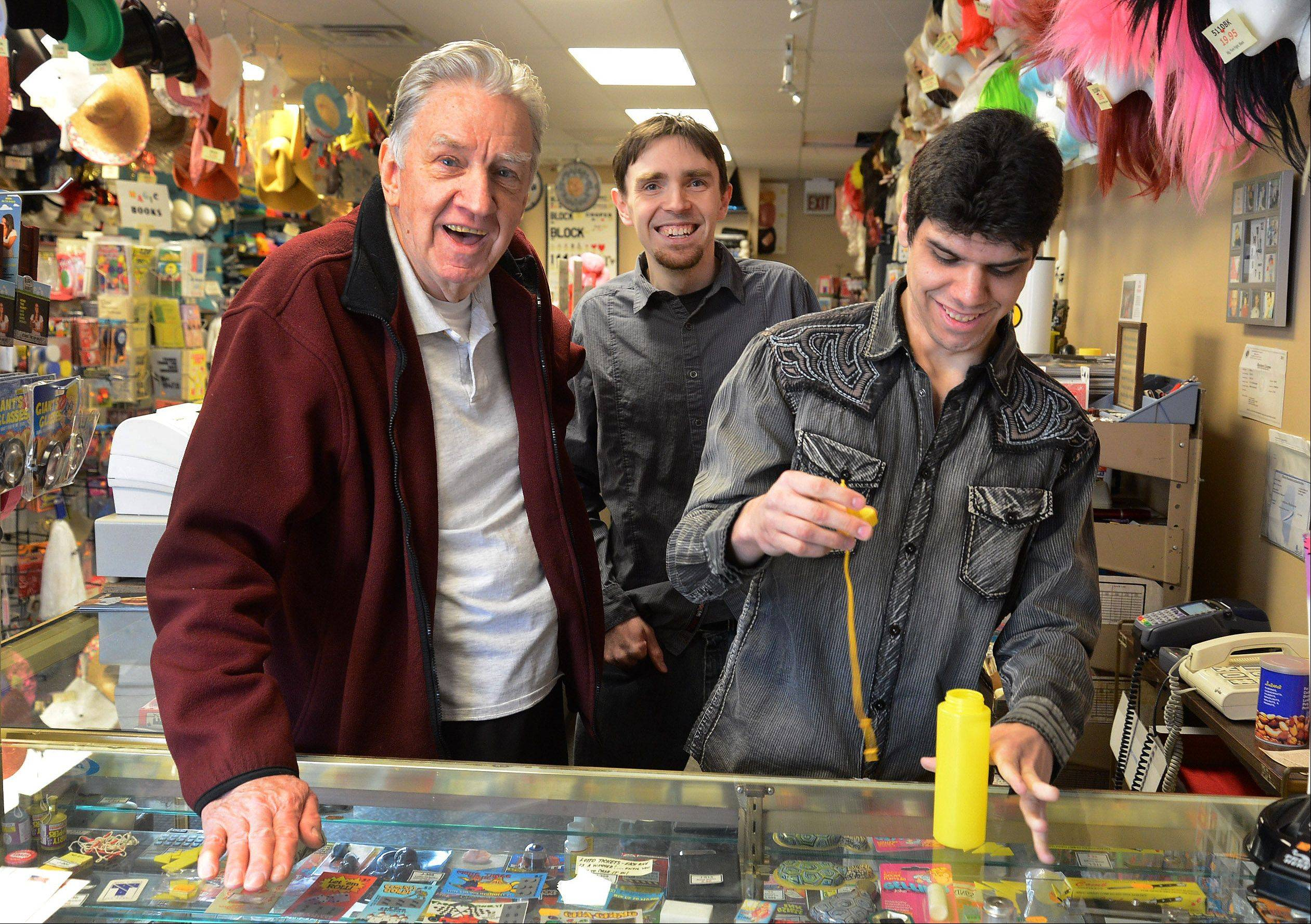 As jokester Trent Rivas reloads the gag mustard squirter, PJ's Trick Shop founder Phil Johnson, left, and his son Brian Johnson can't help but smile during this scene at their store in Arlington Heights.