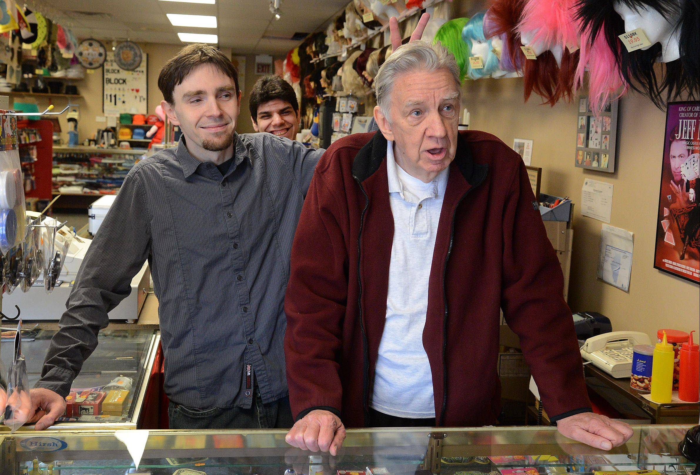 Always mixing in some fun with work, Brian Johnson, left, gives his dad, Phil Johnson, some rabbit ears as a grinning Trent Rivas enjoys the camaraderie at PJ's Trick Shop in Arlington Heights.