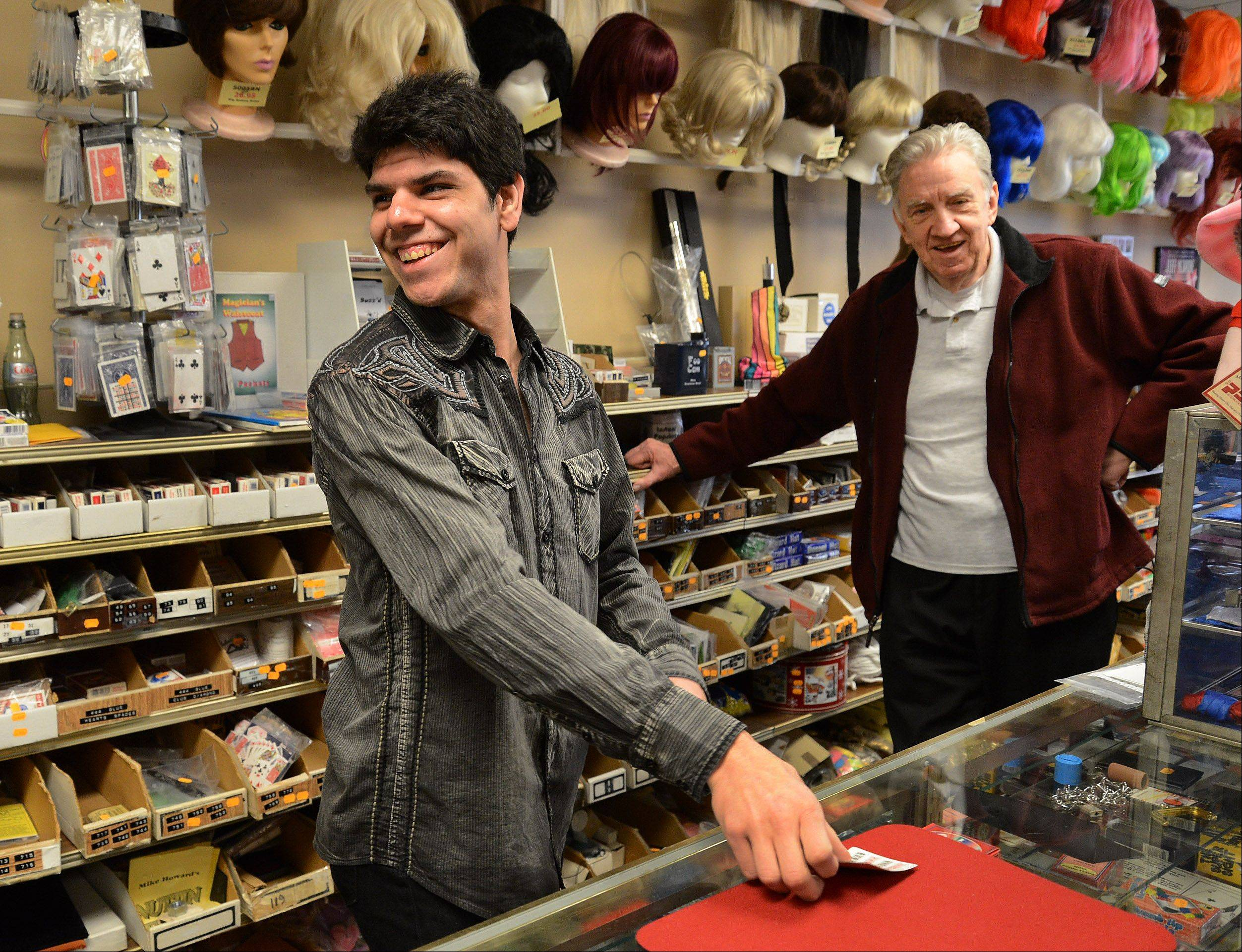 "Developmentally disabled and unable to do simple math or read well, clerk Trent Rivas, left, performs a flawless magic trick under the eye of owner Phil Johnson. ""Magic is almost like therapy for me,"" the 24-year-old Des Plaines resident says."