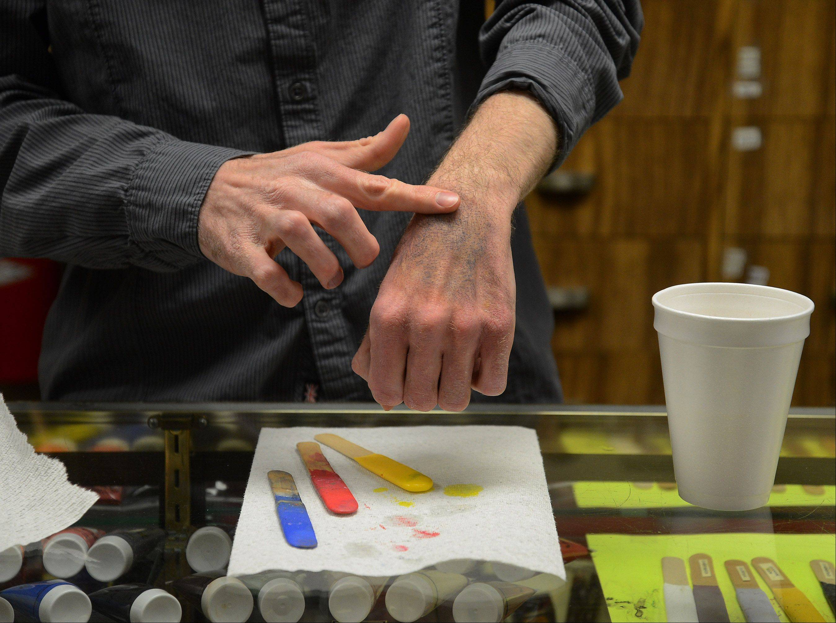 PJ's Trick Shop manager Brian Johnson uses makeup to make a bruise on his hand. The Arlington Heights store has found a new market providing realistic gore for everything from local theater productions to public disaster drills.