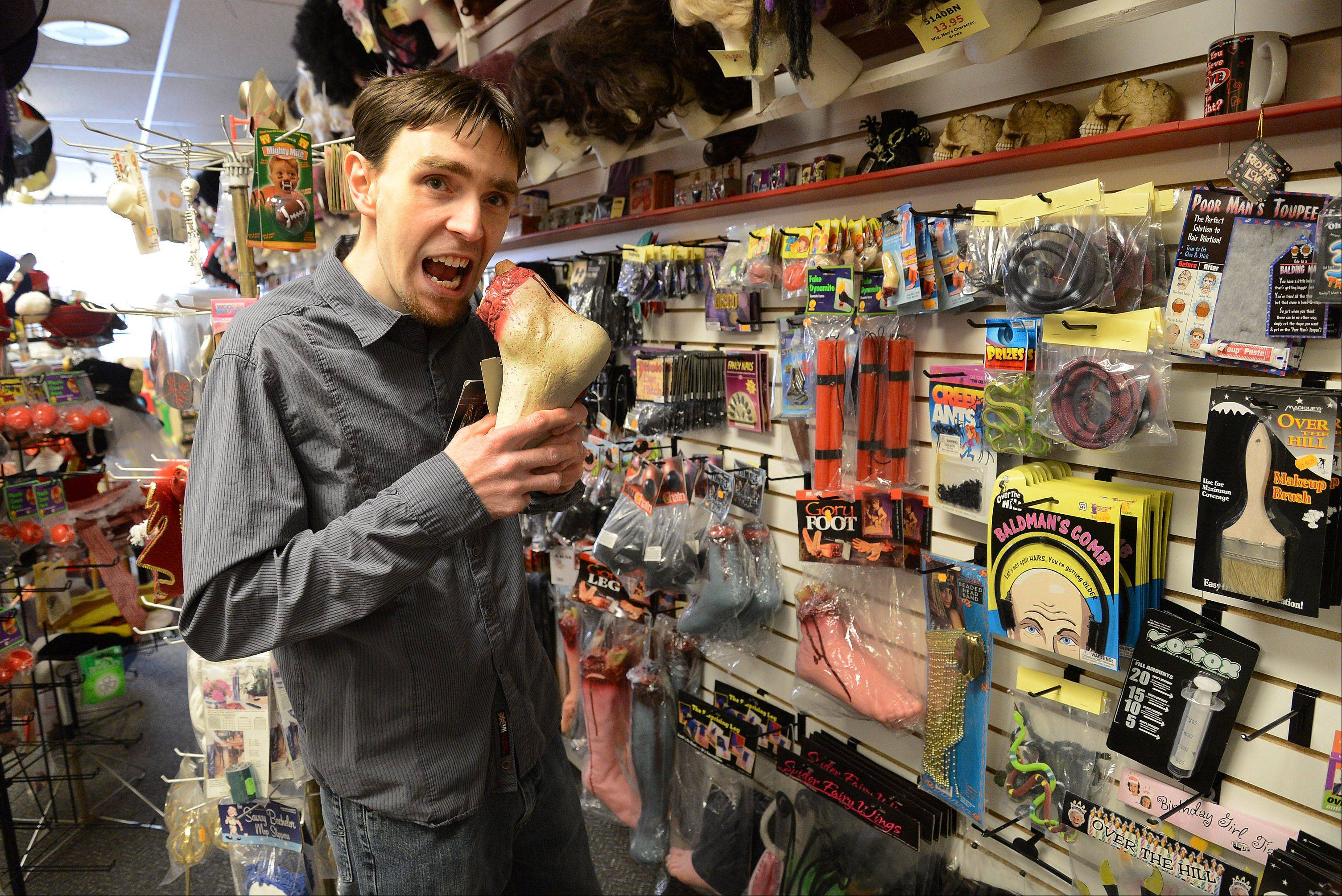 Not above making a joke about having an appetite for gore or a fear of putting his foot in his mouth, manager Brian Johnson chews on a fake foot at PJ's Trick Shop in Arlington Heights.