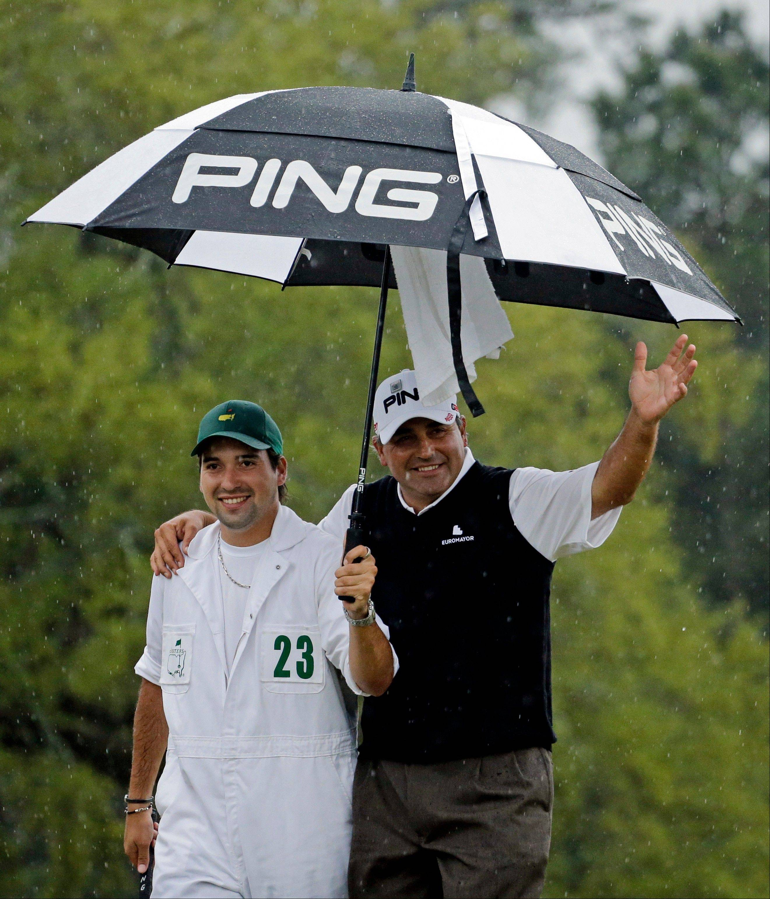 Angel Cabrera, of Argentina, waves with his caddie son after birdie putt on the 18th hole during the fourth round of the Masters golf tournament Sunday, April 14, 2013, in Augusta, Ga.