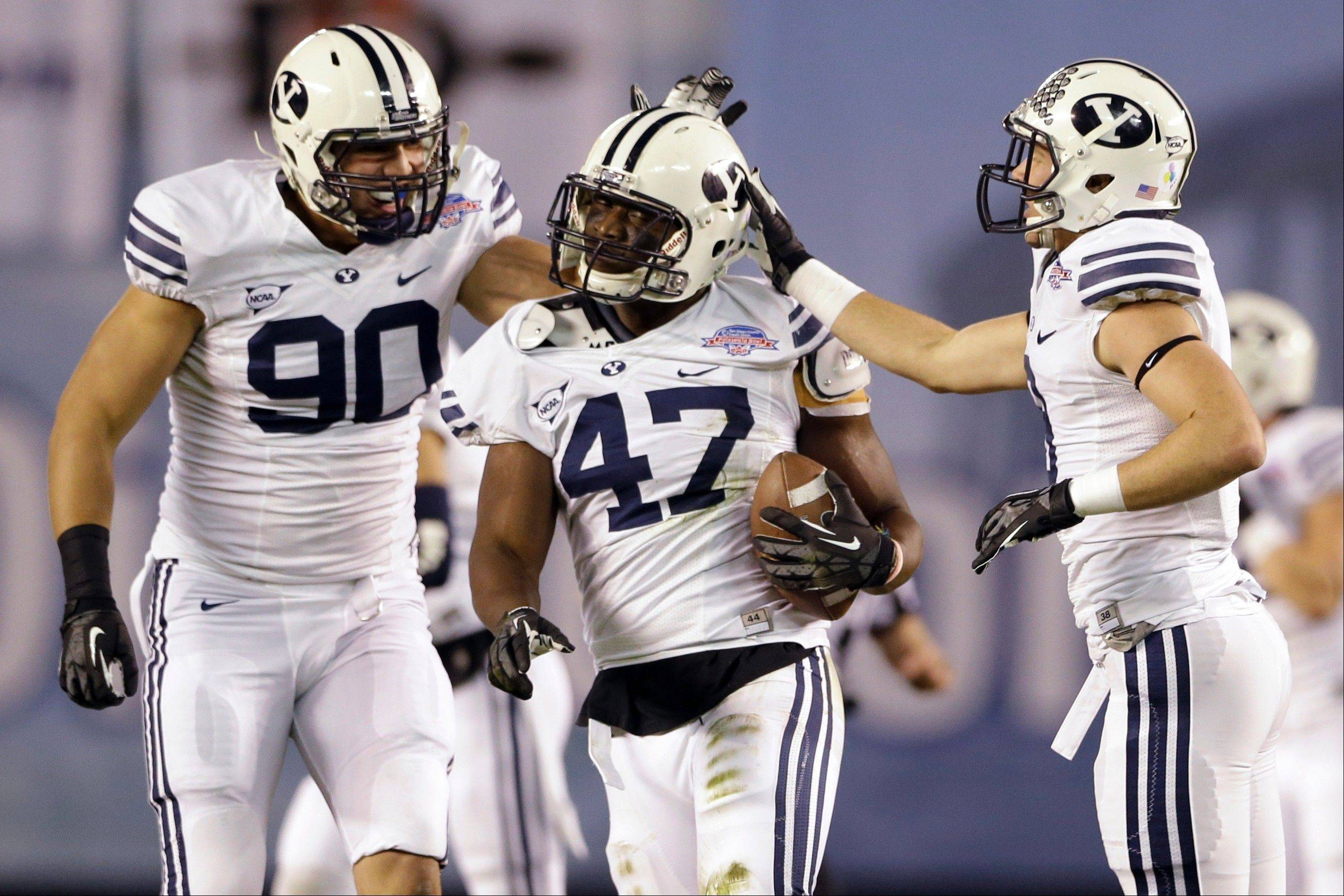 BYU linebacker Ezekiel Ansah, center, is congratulated by Bronson Kaufusi, left, and Daniel Sorensen after intercepting a San Diego State pass during the first half of the Poinsettia Bowl NCAA college football game, Thursday, Dec. 20, 2012, in San Diego.