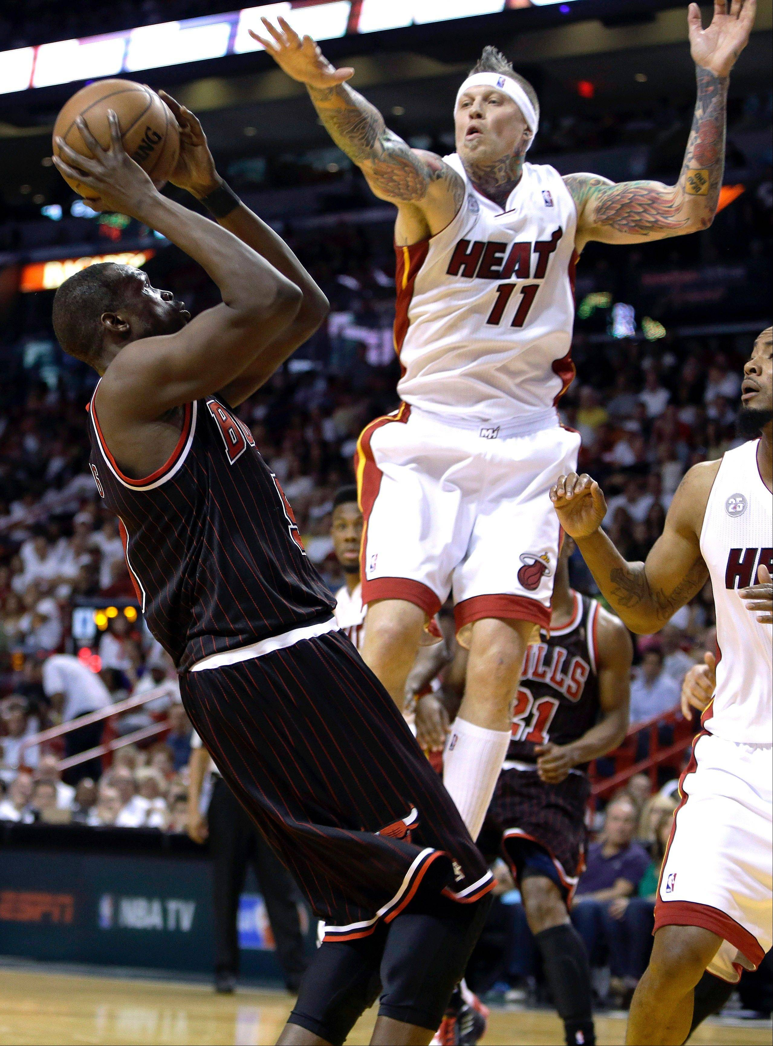 Chicago Bulls' Luol Deng, left, shoots as Miami Heat's Chris Andersen (11) defends during the second half of an NBA basketball game Sunday April 14, 2013, in Miami. The Heat defeated the Bulls 105-93.