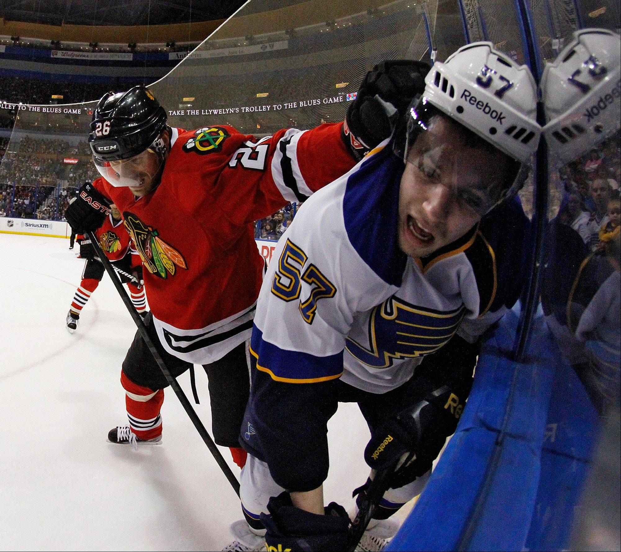 Blackhawks center Michal Handzus, left, pins St. Louis Blues left wing David Perron against the boards in third period action during a game between the Blues and the Blackhawks on Sunday April 14, 2013, at the Scottrade Center in St. Louis.