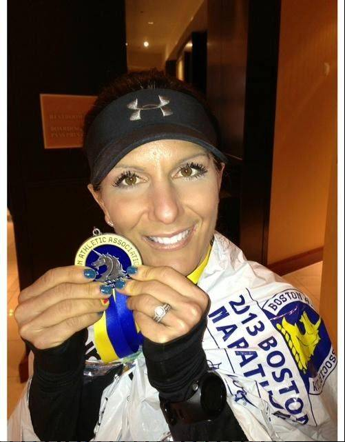 Irene Kok of Huntley holds her medal after finishing the Boston Marathon.