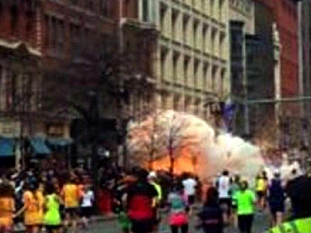 In this image from video provided by WBZ-TV, spectators and runners run from twin explosions that shook the finish line of the Boston Marathon Monday afternoon.
