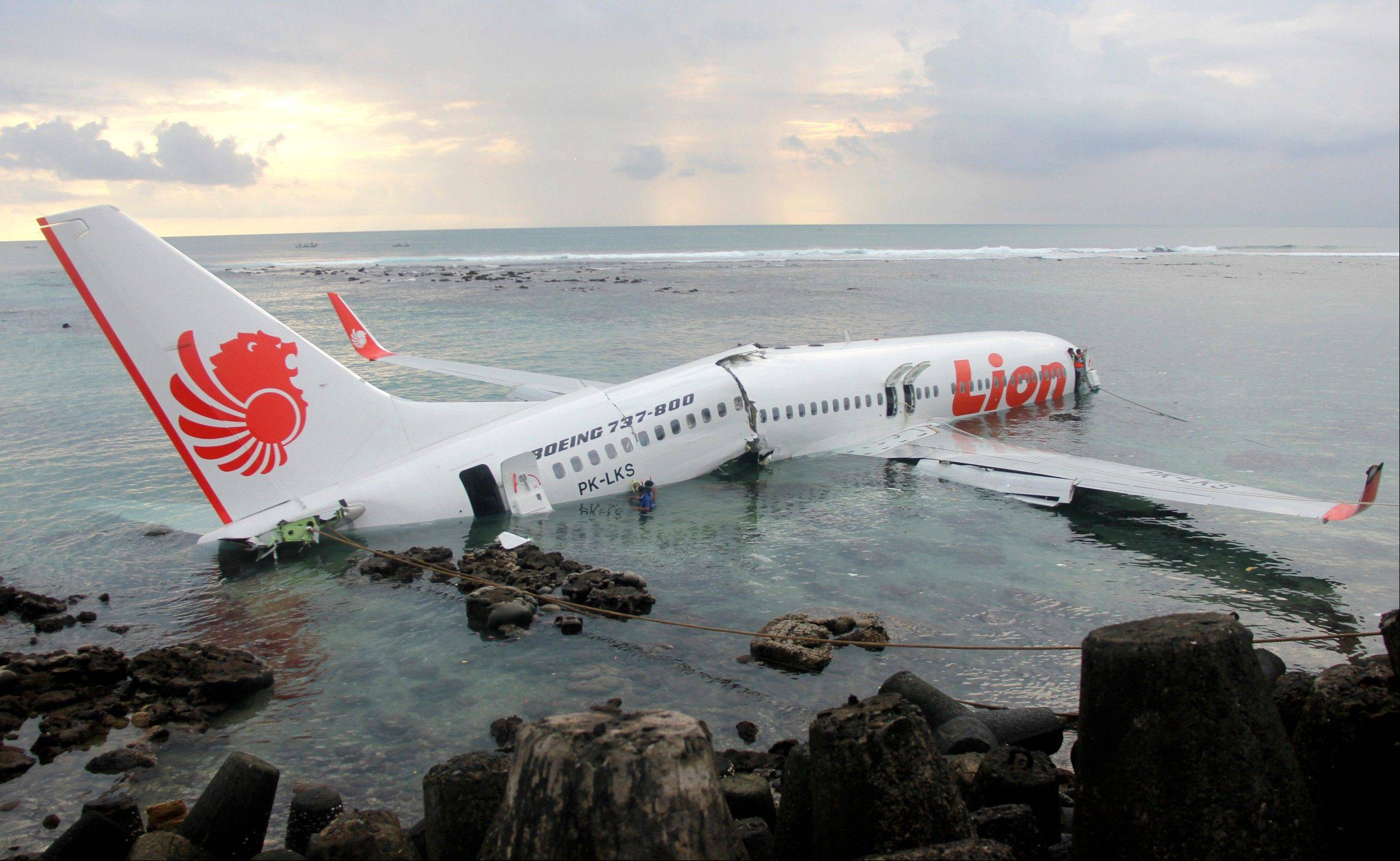 The wreckage of a crashed Lion Air plane in Bali, Indonesia, remains stuck in shallow water Mondayand must be cut into pieces for removal. The plane carrying more than 100 passengers and crew overshot a runway on the Indonesian resort island of Bali on Saturday and crashed into the sea, injuring nearly two dozen people, officials said.