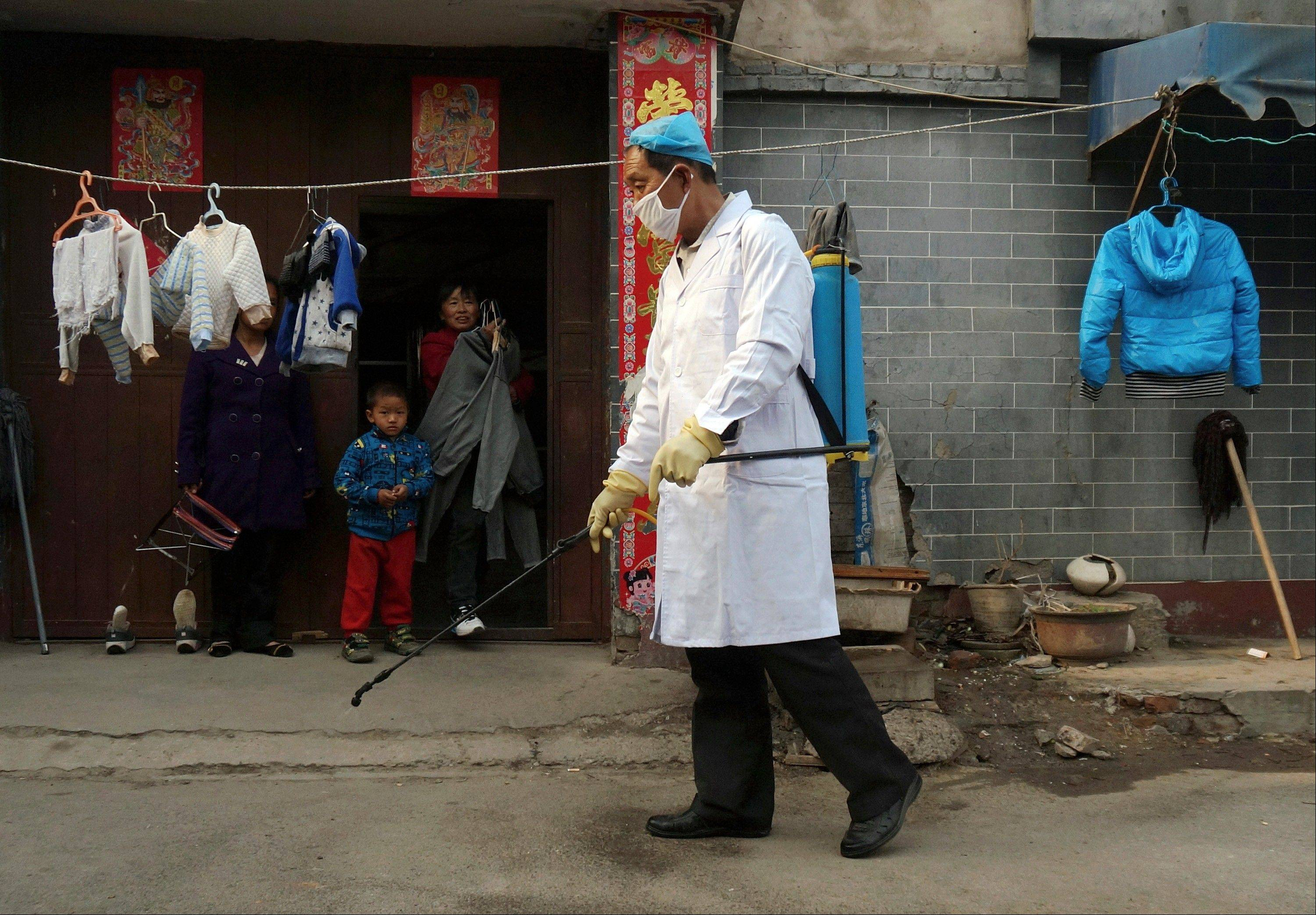 A family watches a worker spray disinfectant in Naidong village, where a boy tested positive for the H7N9 virus, in Beijing Monday. The new case of bird flu in China's capital, a 4-year-old boy who displayed no symptoms, is adding to the unknowns about the latest outbreak that has caused 63 confirmed cases and 14 deaths, health officials said Monday.
