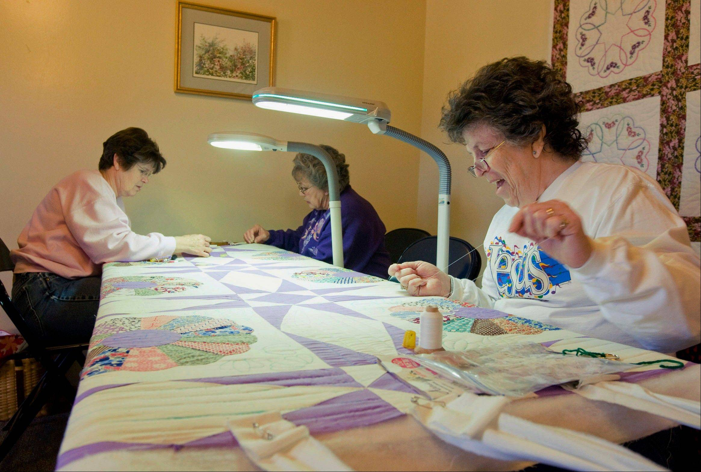 Sarah Altevogt, from right, Mary McLemore and Kathy Pratt sew sections of a quilt at Rock Springs Nature Center in Decatur.