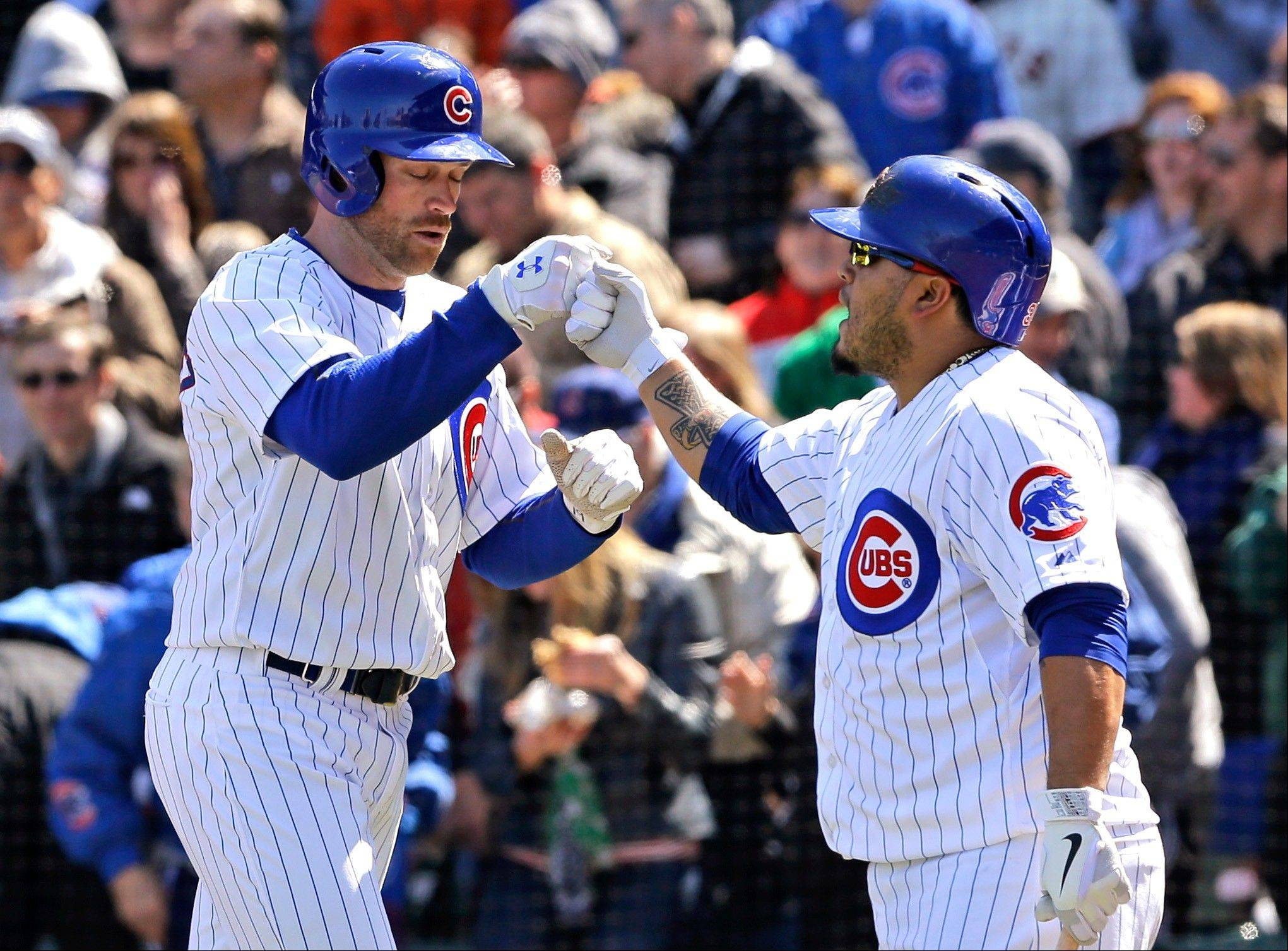 The Cubs� Nate Schierholtz, left, celebrates with Dioner Navarro after hitting a two-run home run during Sunday�s first inning at Wrigley Field.