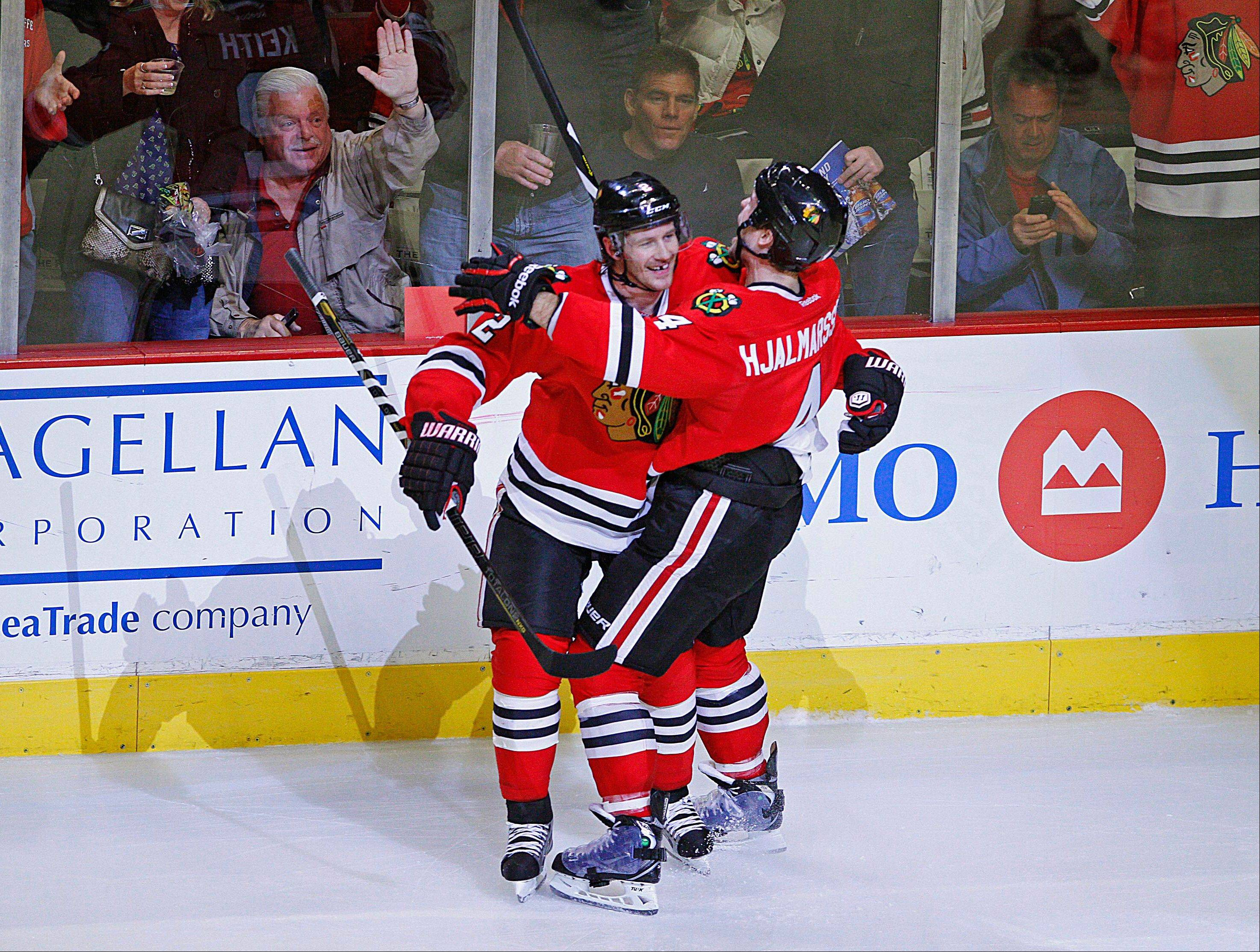 Chicago Blackhawks' Duncan Keith , left, and Niklas Hjalmarsson hug after Hjalmarrsson scored against the Dallas Stars during the third period in an NHL hockey game in Chicago, Monday, April 15, 2013. The Blackhawks won 5-2.