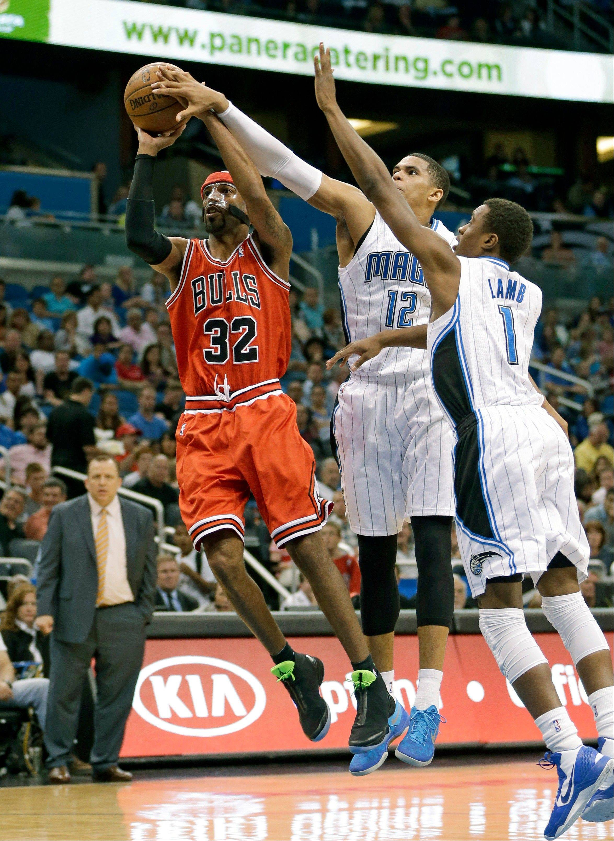 Orlando Magic's Tobias Harris (12) partially blocks a shot by the Bulls' Richard Hamilton (32) as Doron Lamb (1) comes in to assist during the first half of the game, Monday in Orlando. The Bulls won 102-84.