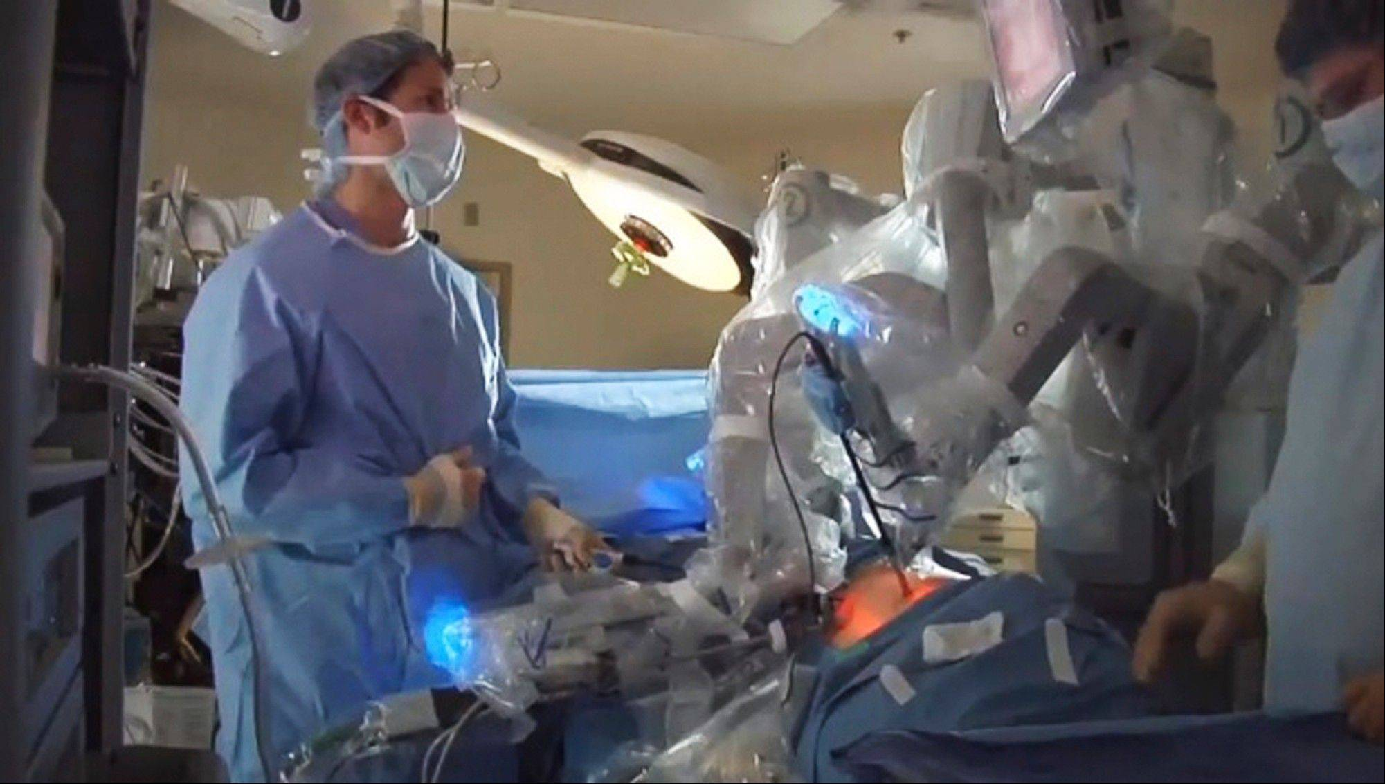 Doctors use the da Vinci robotic system to perform a surgery. Surgeons say the advantages of the system include allowing them to operate sitting down, using small robotic hands with no tremor. But critics say a big increase in robot operations nationwide is due to heavy marketing and hype.