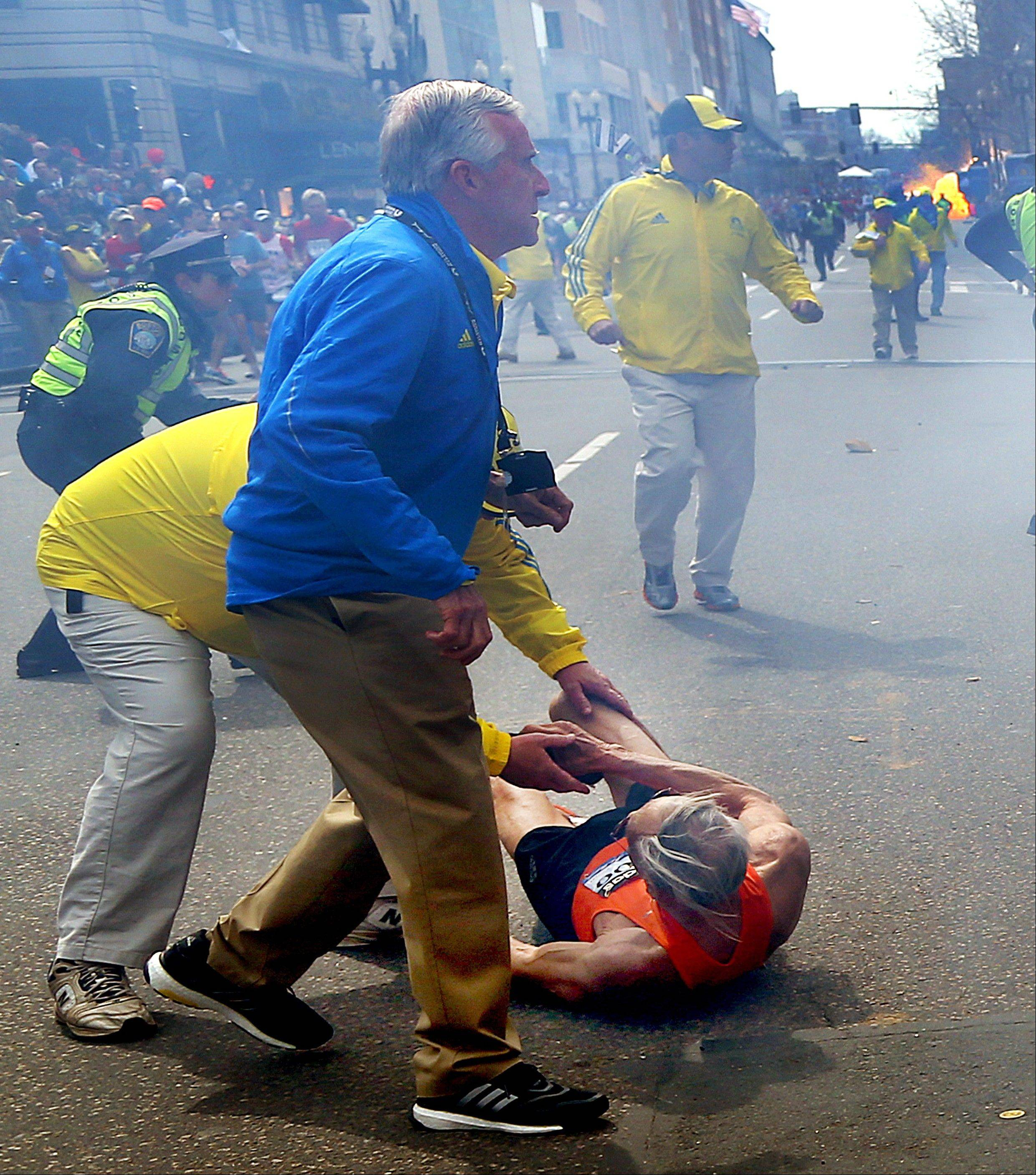 People react to a second explosion at the Boston Marathon Monday afternoon. Authorities ran out on the course to carry off the injured while the stragglers were rerouted away from the smoking site of the blasts.