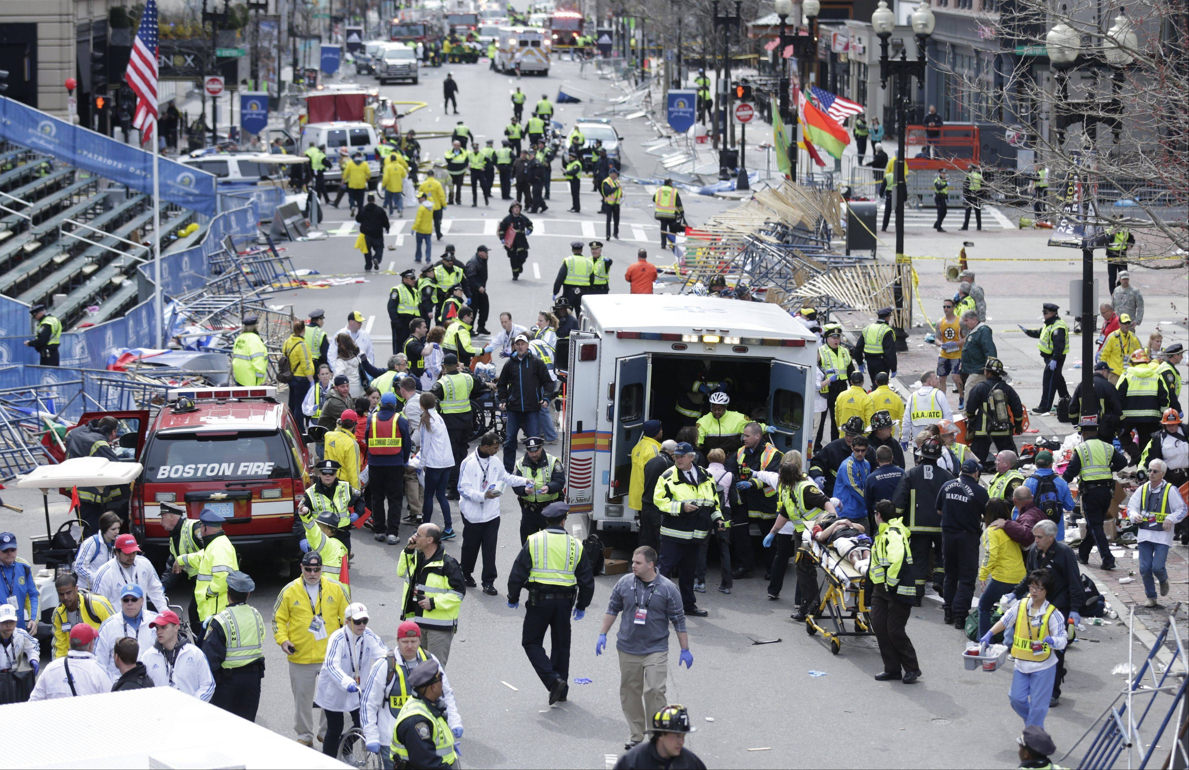 Medical workers aid injured people at the finish line of the Boston Marathon following Monday's explosion.