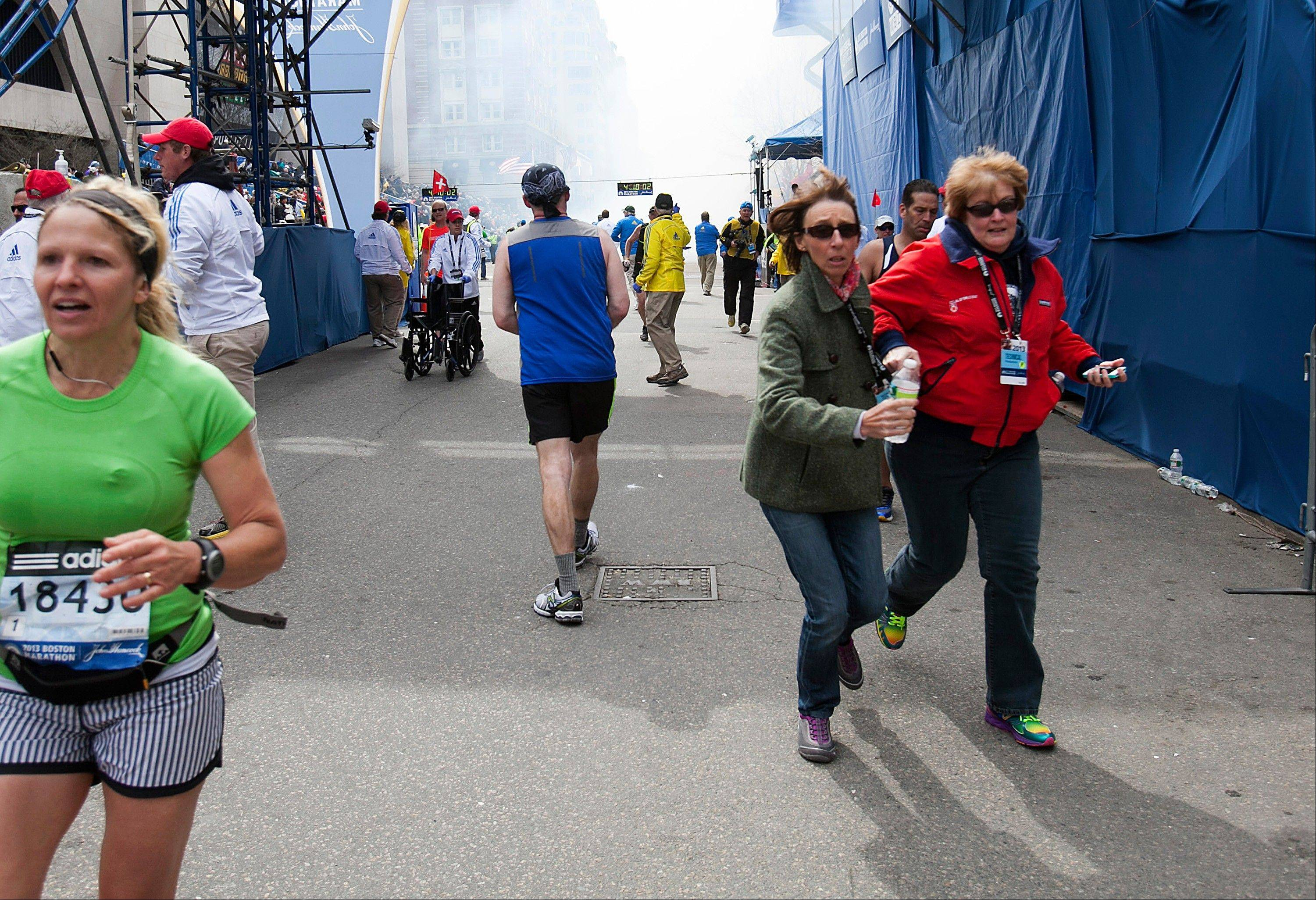 Runners and spectators flee from the scene where two explosions occurred along the final stretch of the Boston Marathon on Boylston Street in Boston, Massachusetts, U.S., on Monday, April 15, 2013. Two powerful explosions rocked the finish line area of the Boston Marathon near Copley Square and police said many people were injured.