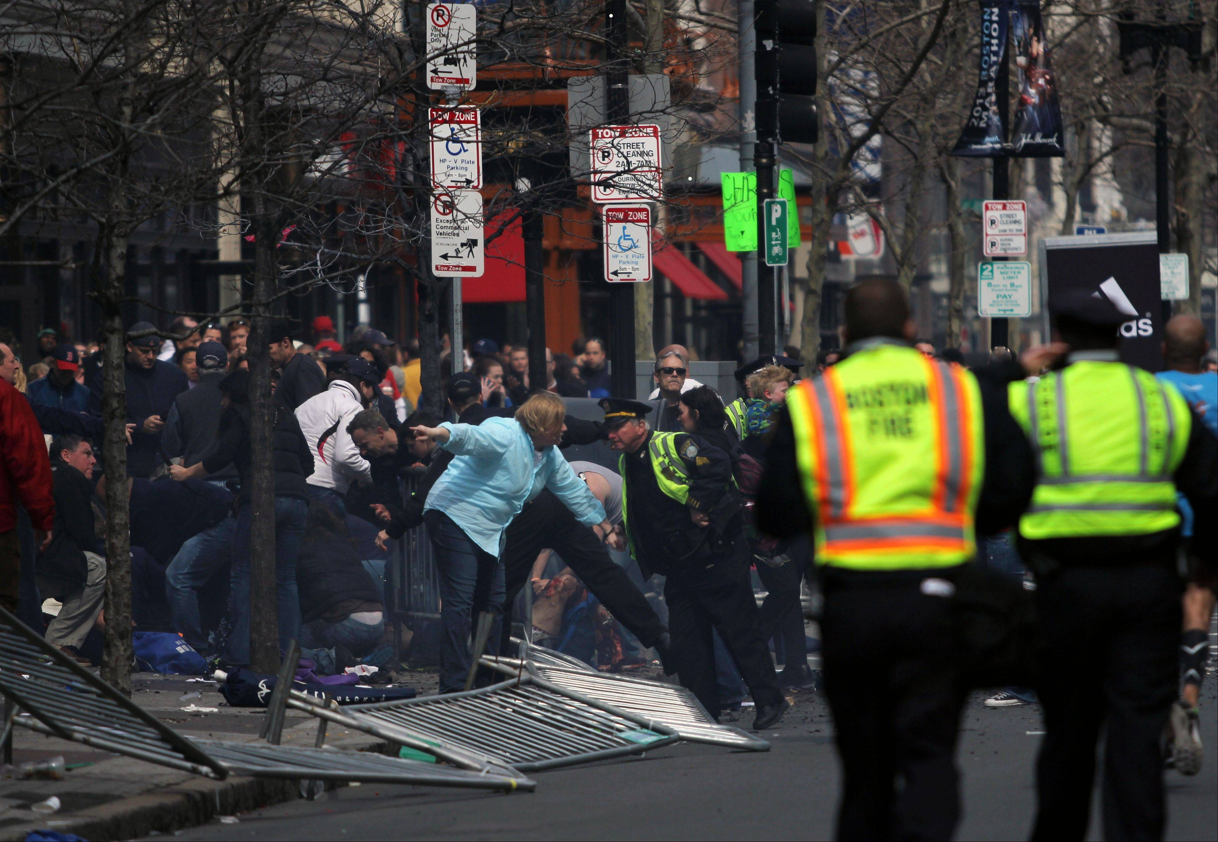 In this photo provided by The Daily Free Press and Kenshin Okubo, people react to an explosion at the 2013 Boston Marathon in Boston, Monday, April 15, 2013.