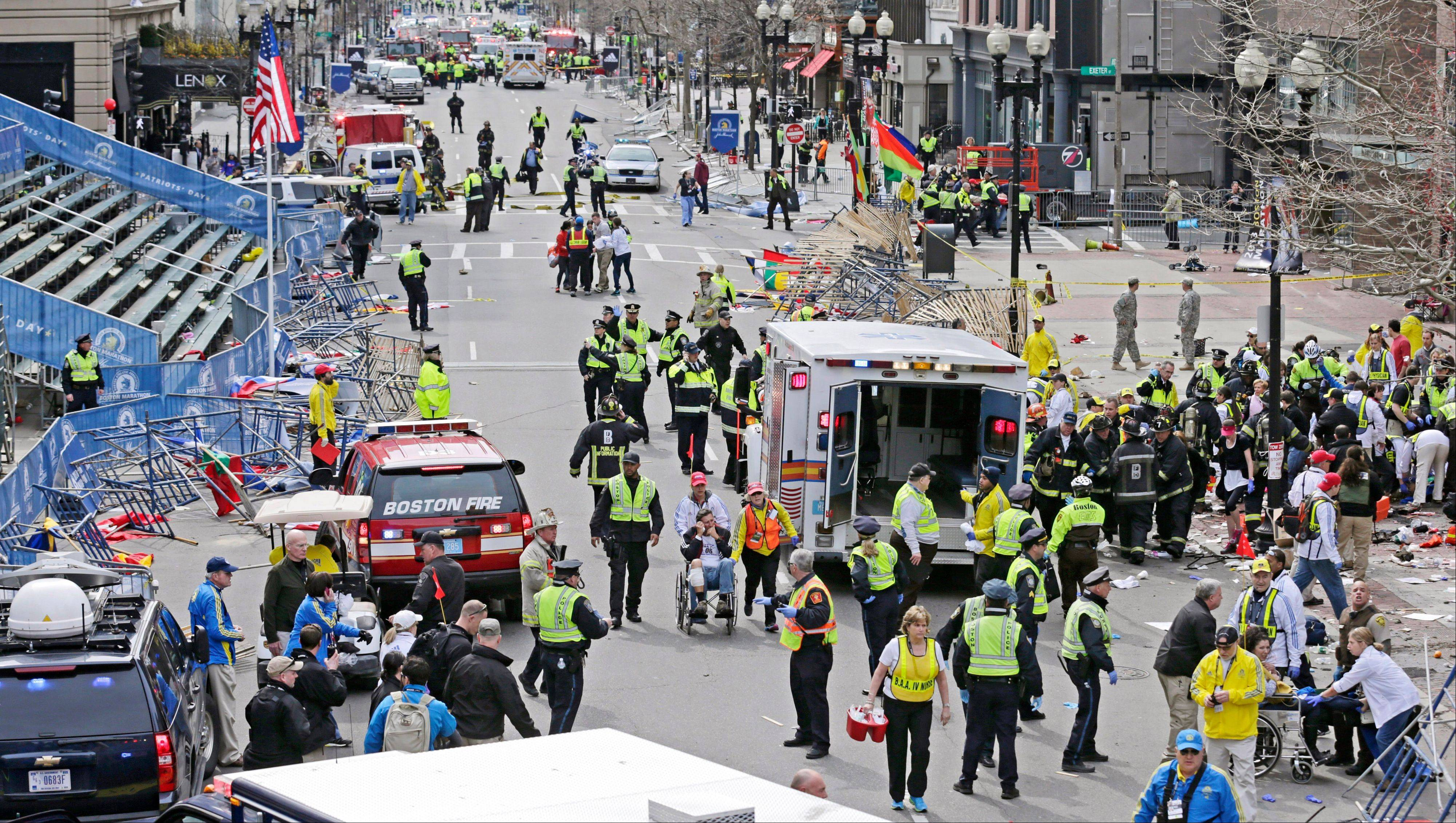 Medical workers aid injured people at the finish line of the 2013 Boston Marathon following explosions in Boston, Monday, April 15, 2013. Two explosions shattered the euphoria of the Boston Marathon finish line on Monday, sending authorities out on the course to carry off the injured while the stragglers were rerouted away from the smoking site of the blasts.