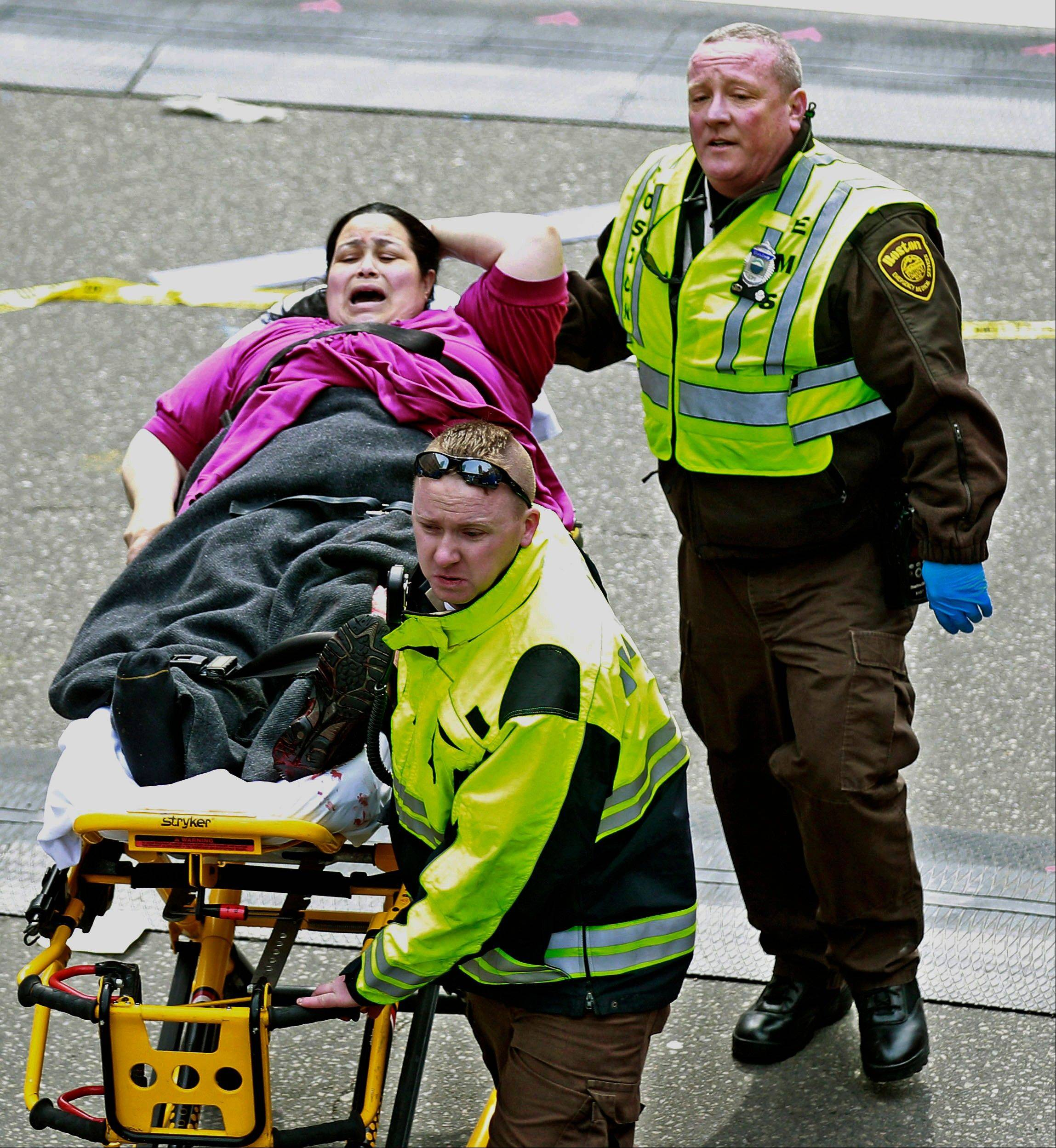Medical workers aid an injured woman at the finish line of the 2013 Boston Marathon following two explosions there, Monday, April 15, 2013 in Boston. Two bombs exploded near the finish of the Boston Marathon on Monday, killing at least two people, injuring at least 23 others and sending authorities rushing to aid wounded spectators.