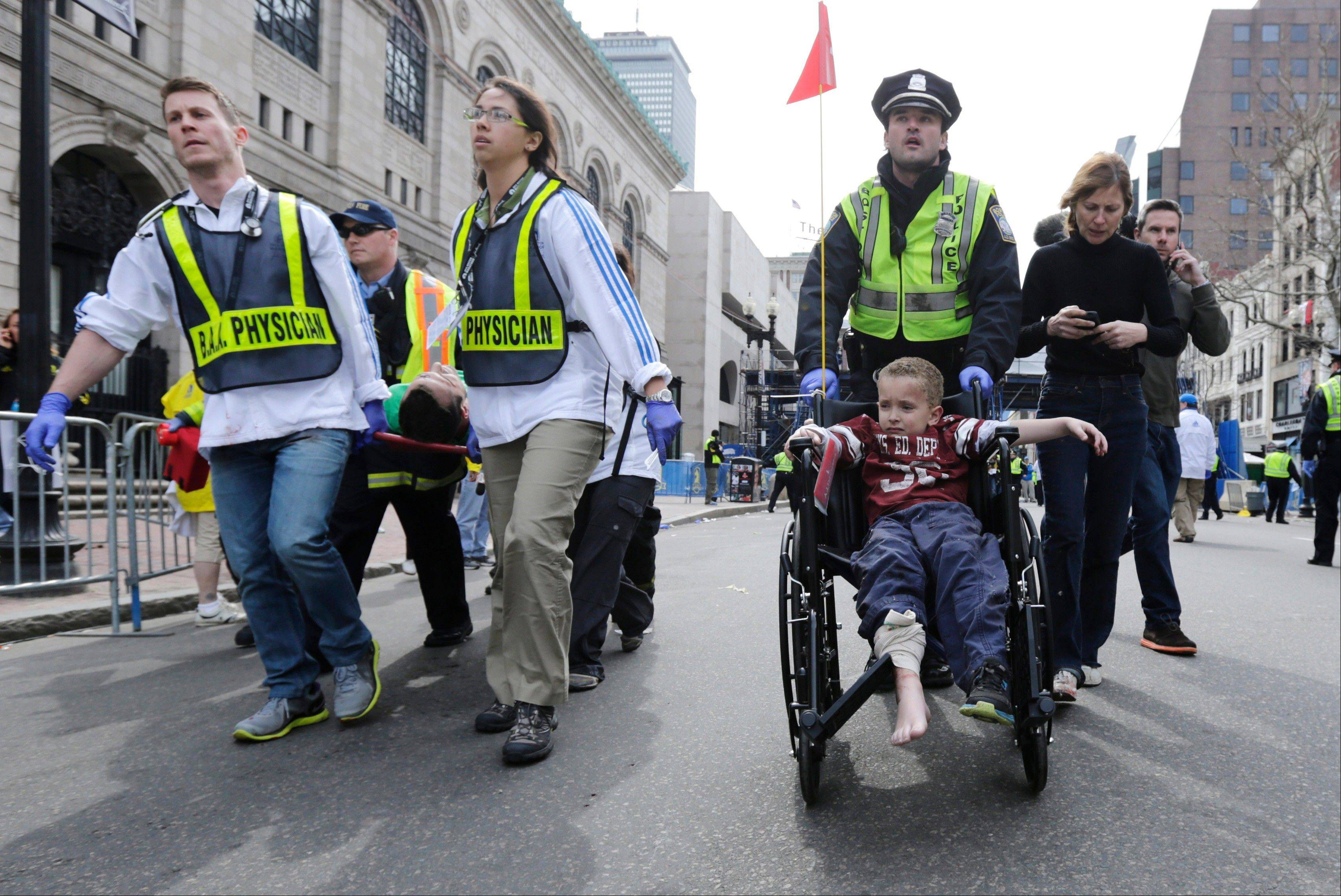 A Boston police officer wheels in injured boy down Boylston Street as medical workers carry an injured runner following an explosion during the 2013 Boston Marathon in Boston, Monday, April 15, 2013. Two explosions shattered the euphoria at the marathon's finish line on Monday, sending authorities out on the course to carry off the injured while the stragglers were rerouted away from the smoking site of the blasts.