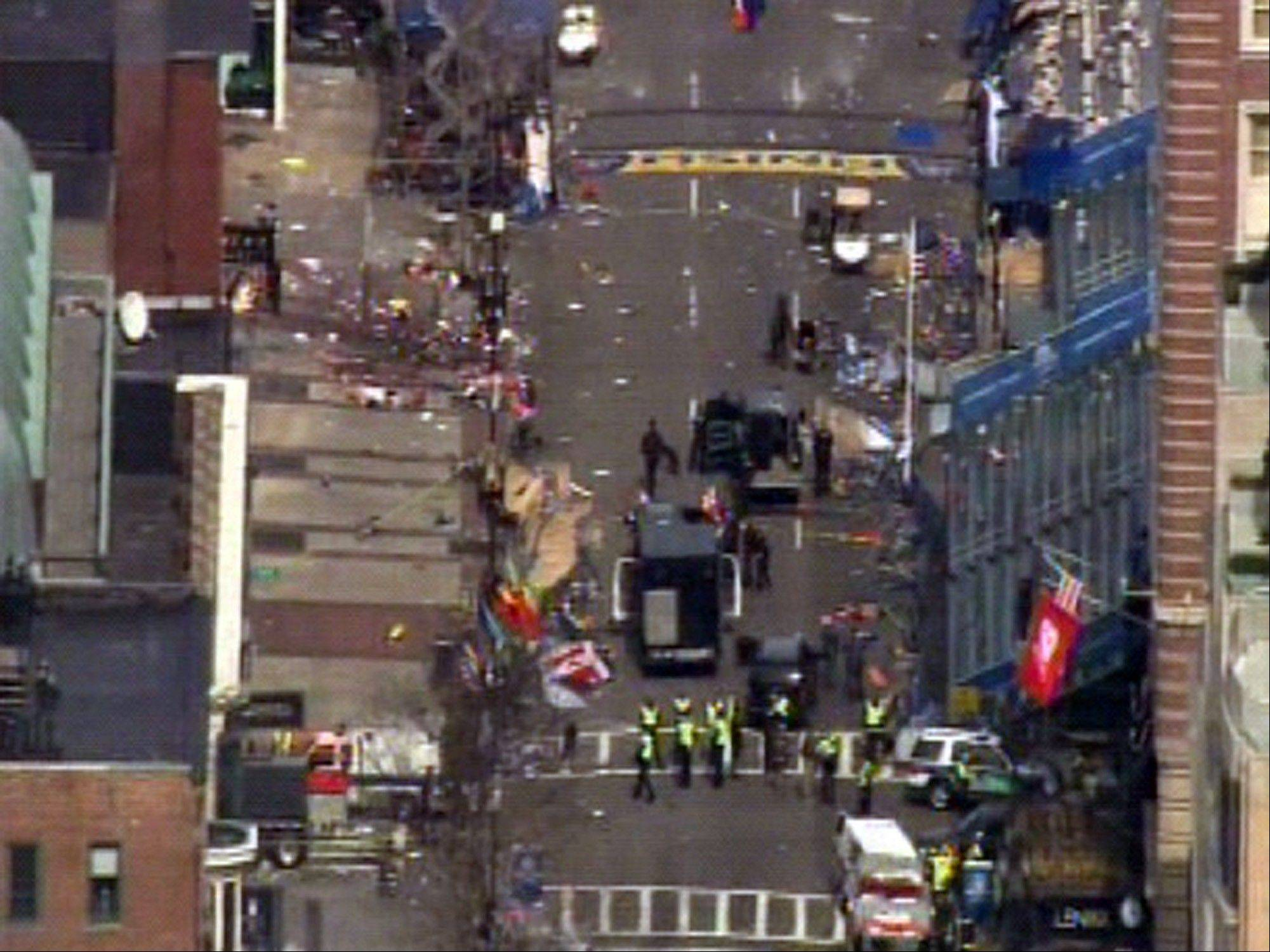 Medical workers and authorities work on the scene near the finish line of the 2013 Boston Marathon following an explosion in Boston, Monday, April 15, 2013.