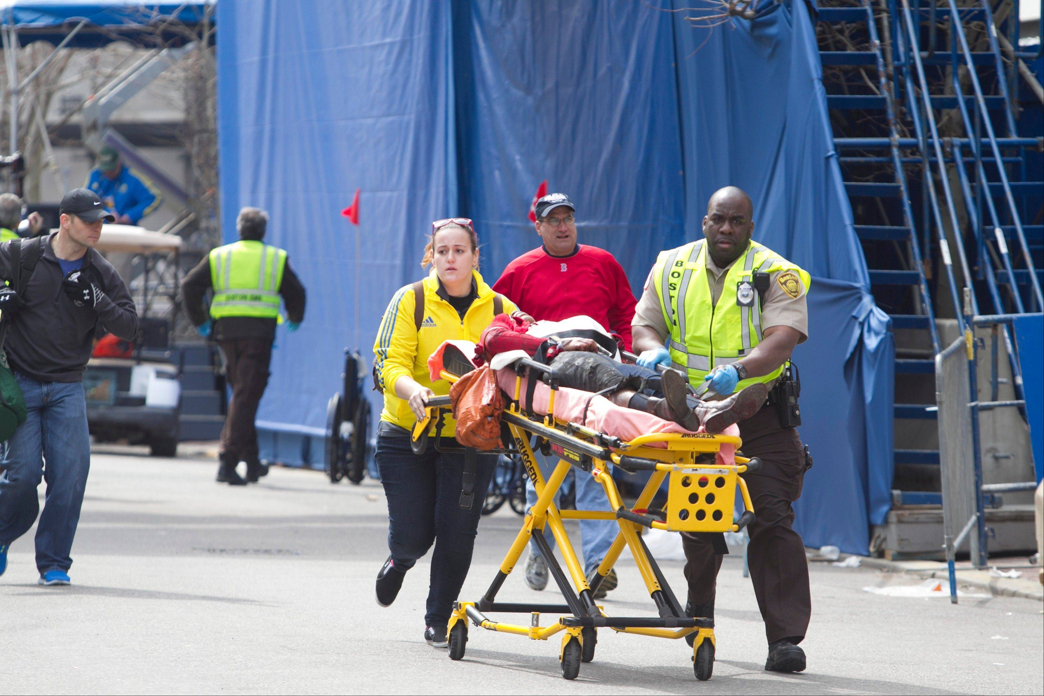 First responders transport the wounded where two explosions occurred along the final stretch of the Boston Marathon on Boylston Street in Boston, Massachusetts, U.S., on Monday, April 15, 2013. Two powerful explosions rocked the finish line area of the Boston Marathon near Copley Square and police said many people were injured.