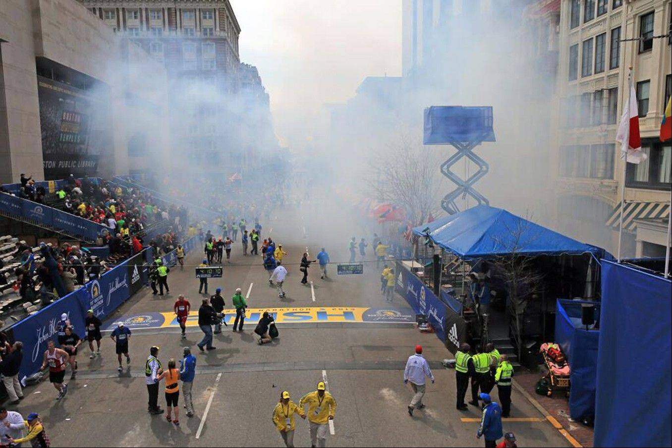 Medical workers aid injured people at the 2013 Boston Marathon following an explosion in Boston, Monday, April 15, 2013. Two explosions shattered the euphoria of the Boston Marathon finish line on Monday, sending authorities out on the course to carry off the injured while the stragglers were rerouted away from the smoking site of the blasts.