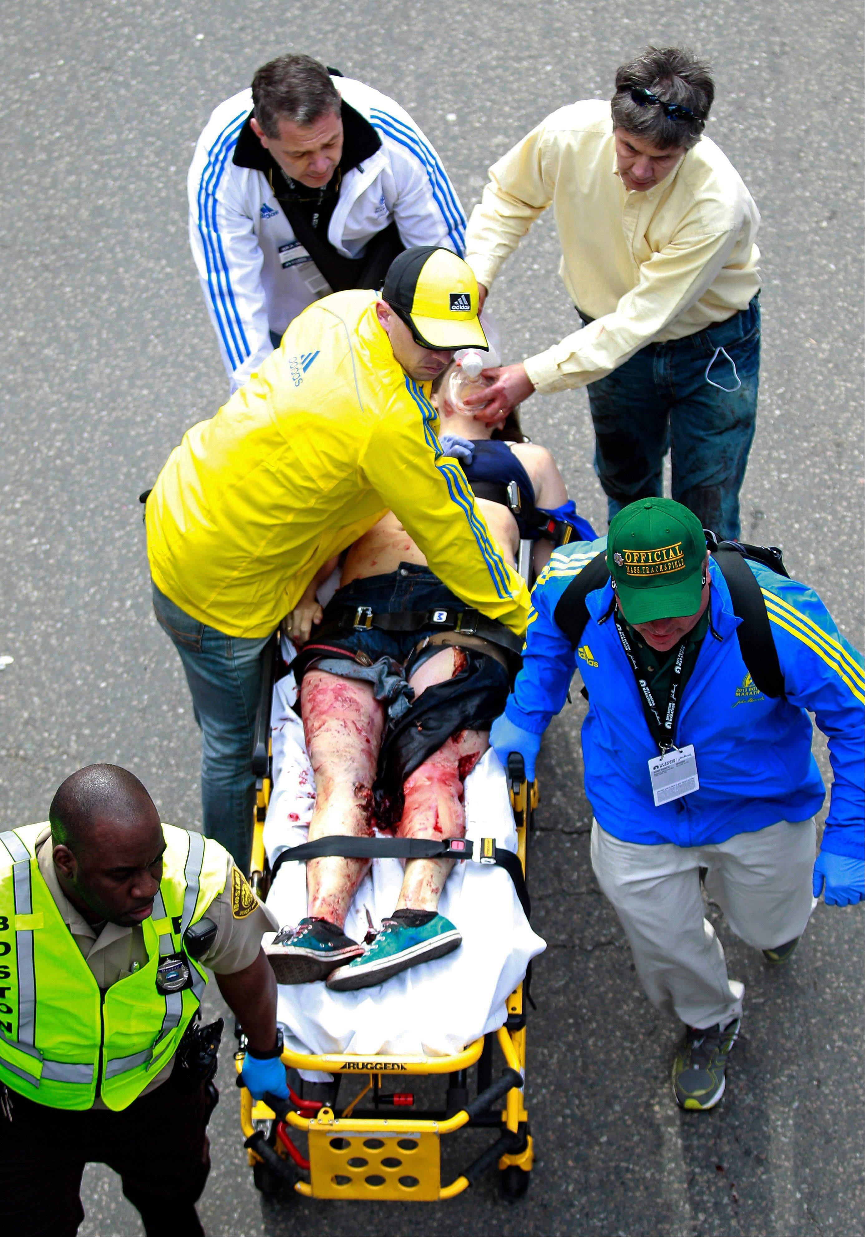 Medical workers aid an injured man at the finish line of the 2013 Boston Marathon following an explosion in Boston, Monday, April 15, 2013. Two bombs exploded near the finish of the Boston Marathon on Monday, killing two people, injuring 22 others and sending authorities rushing to aid wounded spectators, race organizers and police said.
