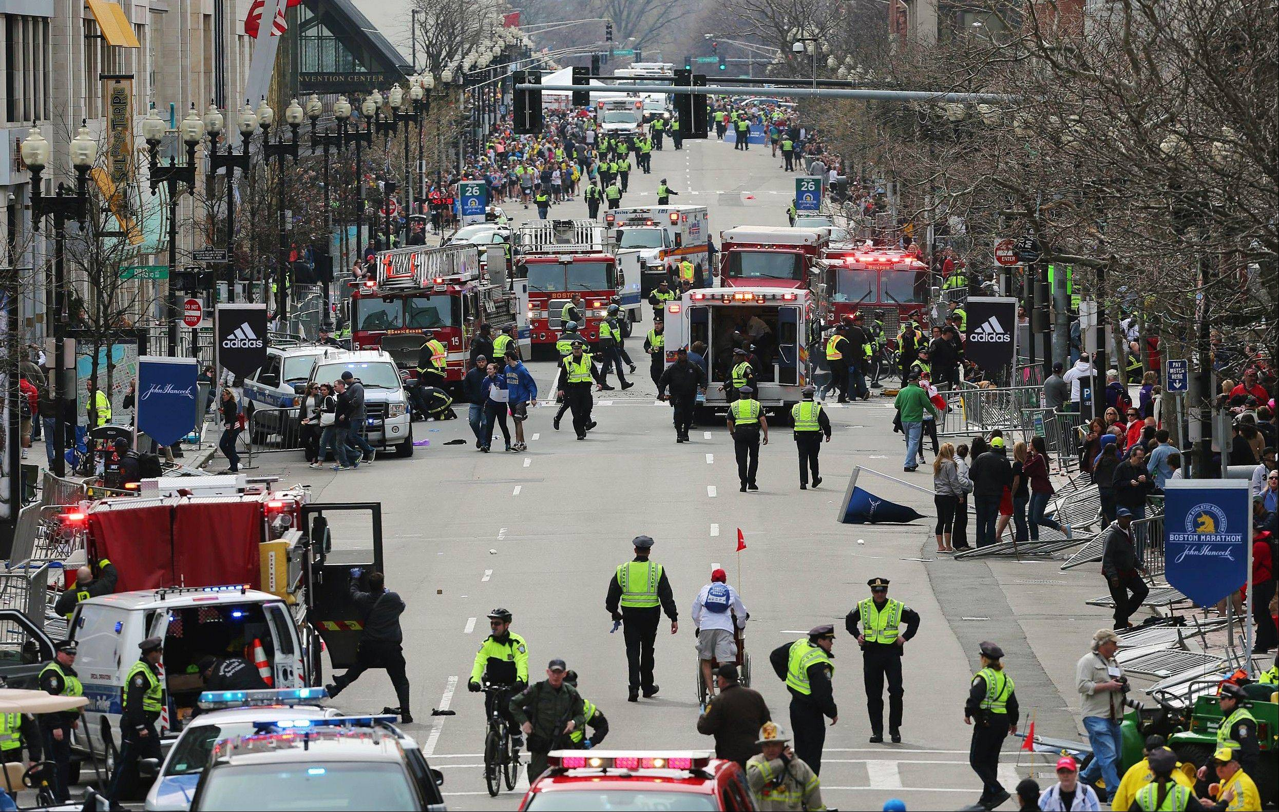 Medical workers respond following an explosion at the 2013 Boston Marathon in Boston, Monday, April 15, 2013. Two explosions shattered the euphoria of the Boston Marathon finish line on Monday, sending authorities out on the course to carry off the injured while the stragglers were rerouted away from the smoking site of the blasts.