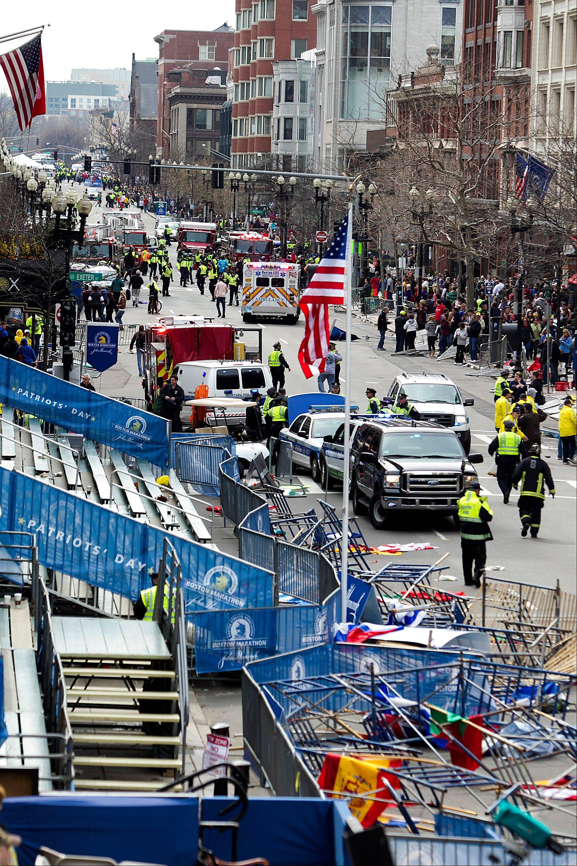 First responders rush to where two explosions occurred along the final stretch of the Boston Marathon on Boylston Street in Boston, Massachusetts, U.S., on Monday, April 15, 2013. Two powerful explosions rocked the finish line area of the Boston Marathon near Copley Square and police said many people were injured.