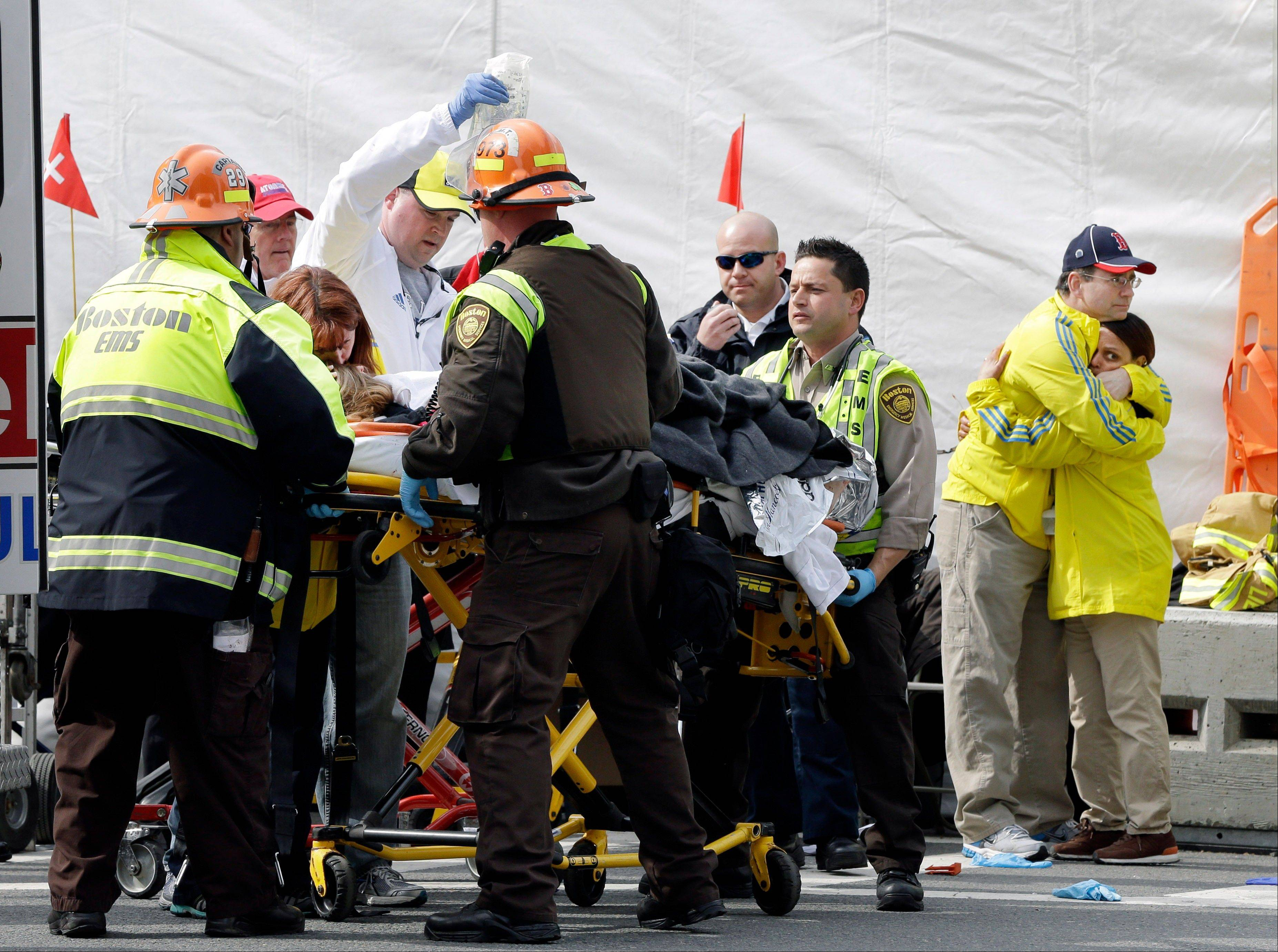 Two Boston Marathon volunteers hug each other, at right, as an injured person is loaded into an ambulance in the aftermath of two blasts which exploded near the finish line of the Boston Marathon in Boston, Monday, April 15, 2013.