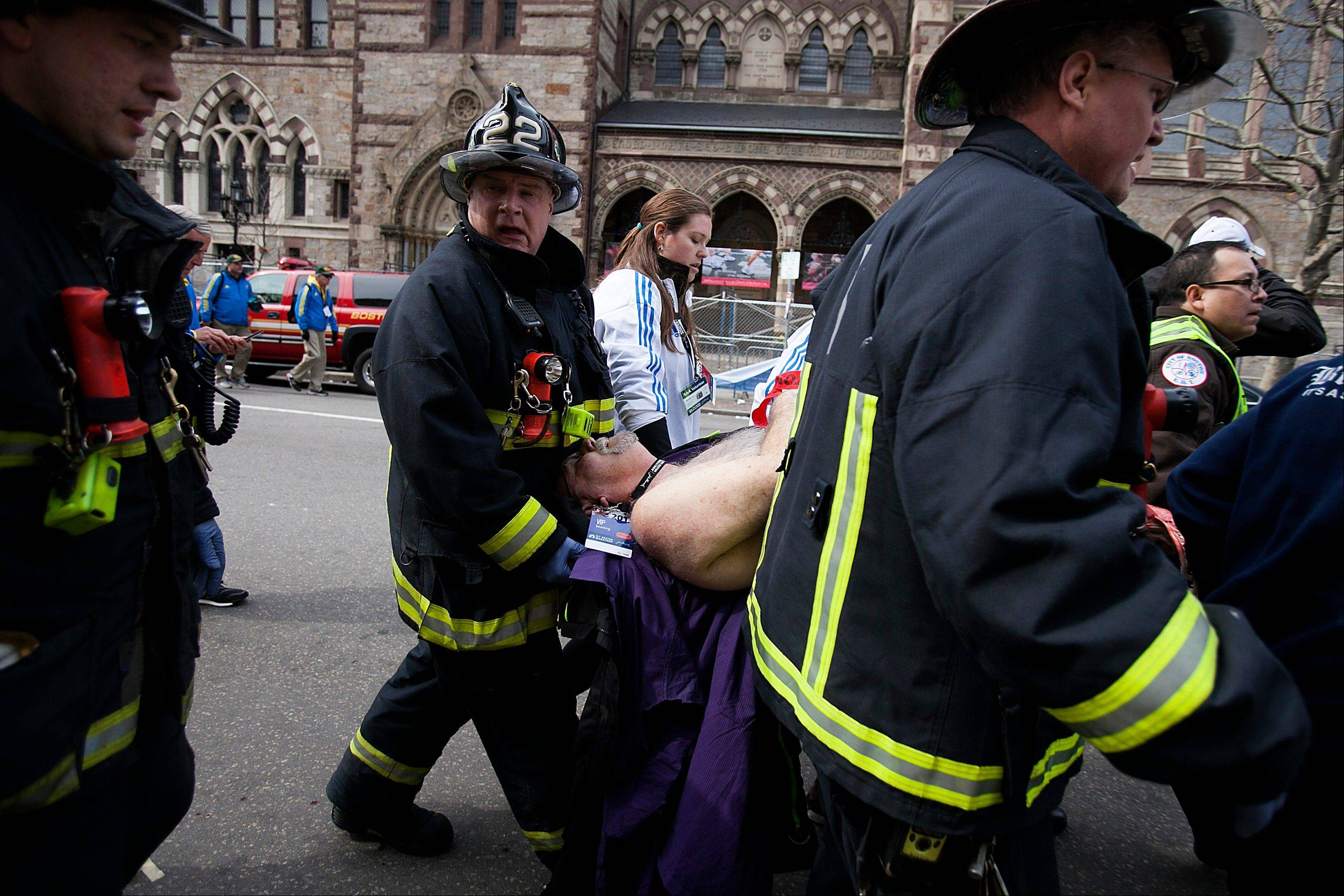 Firemen carry an injured person where two explosions occurred along the final stretch of the Boston Marathon on Boylston Street in Boston, Massachusetts, U.S., on Monday, April 15, 2013. Two powerful explosions rocked the finish line area of the Boston Marathon near Copley Square and police said many people were injured.