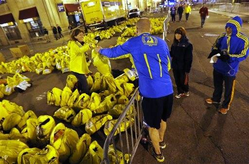 A runner retrieves his belongings from a Boston Athletics Association worker at a sorting area near the site of an explosion at the finish line of the Boston Marathon in Boston, Monday, April 15, 2013.