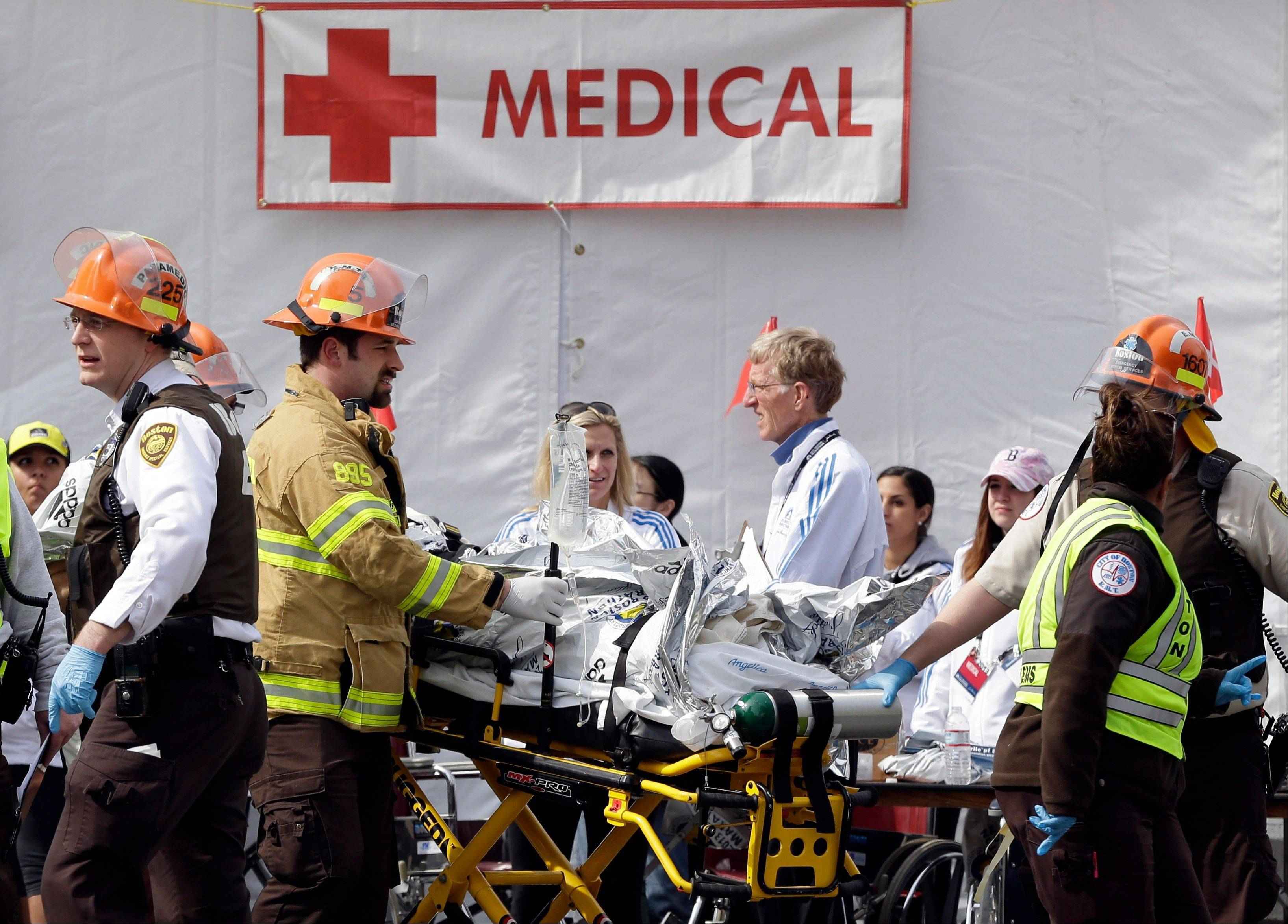 Medical personnel work outside the medical tent in the aftermath of two blasts which exploded near the finish line of the Boston Marathon in Boston, Monday, April 15, 2013.