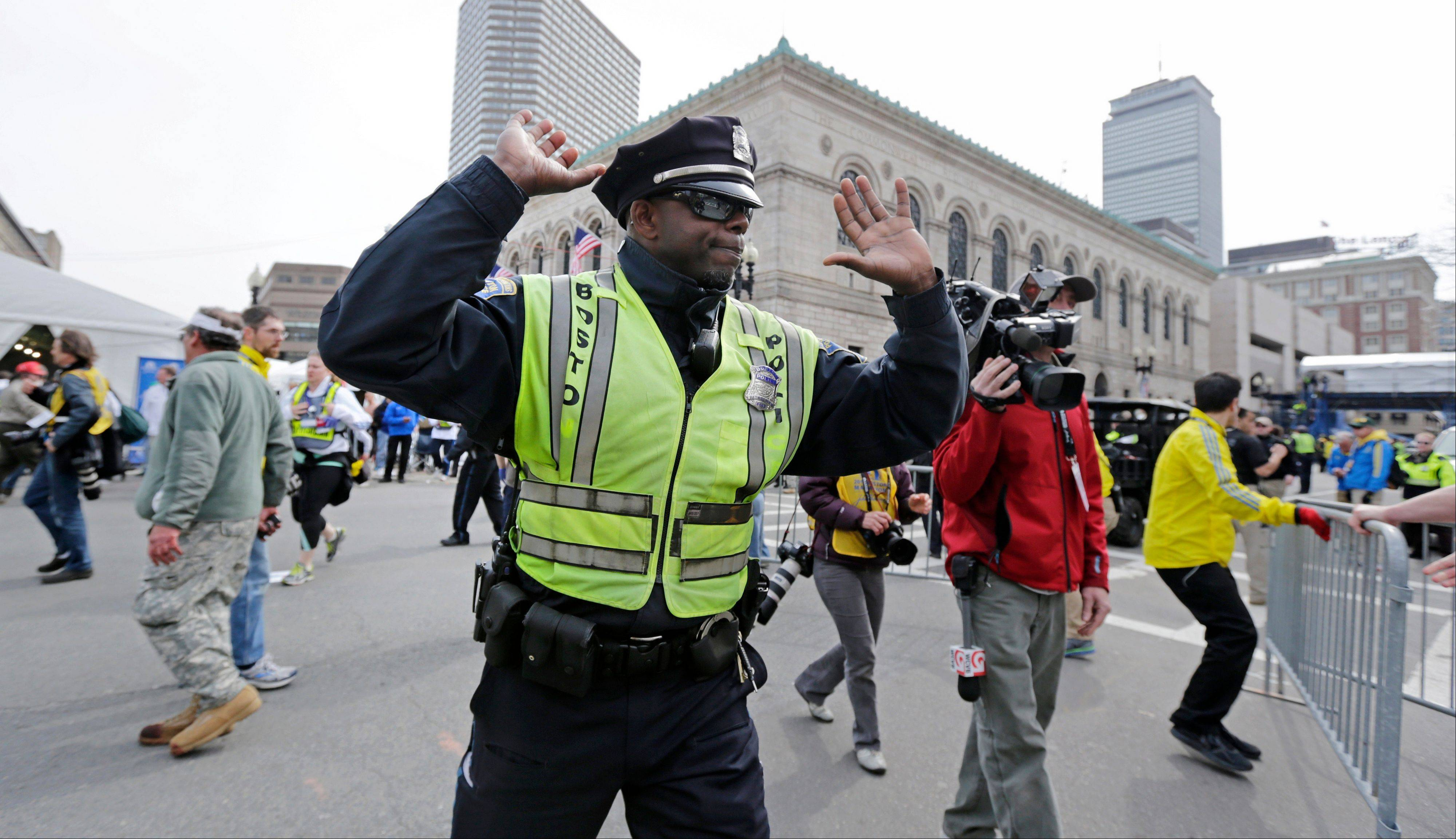 A Boston police officer clears Boylston Street following an explosion at the finish line of the 2013 Boston Marathon in Boston, Monday, April 15, 2013. Two explosions shattered the euphoria at the finish line on Monday, sending authorities out on the course to carry off the injured while the stragglers were rerouted away from the smoking site of the blasts.