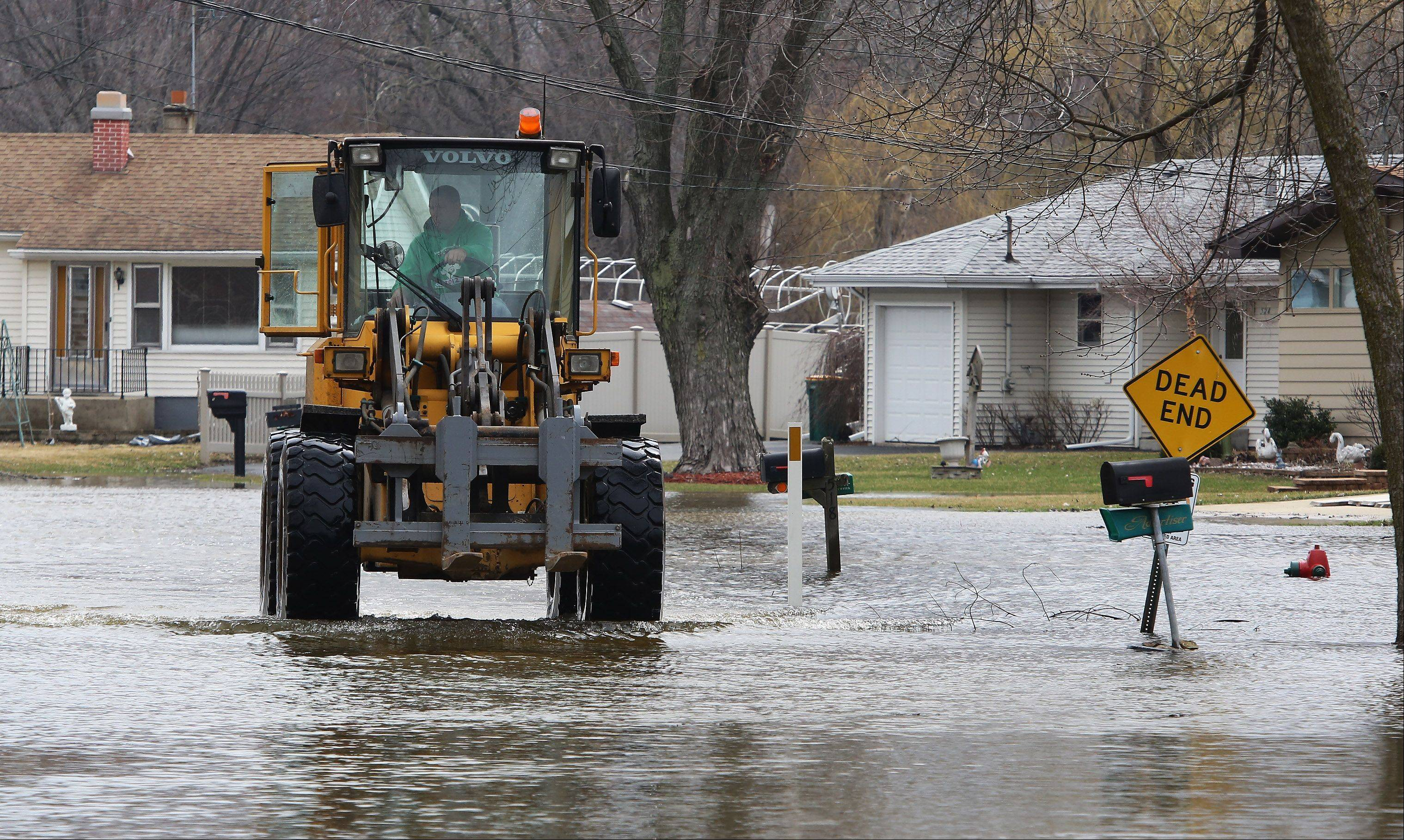 Dana Magness of the Fox Lake Street Department drives through Bayview Marina after delivering a pallet of sand bags Monday for residents along the lake. Residents are watching the weather and concerned about flooding along the Fox River in Lake County.