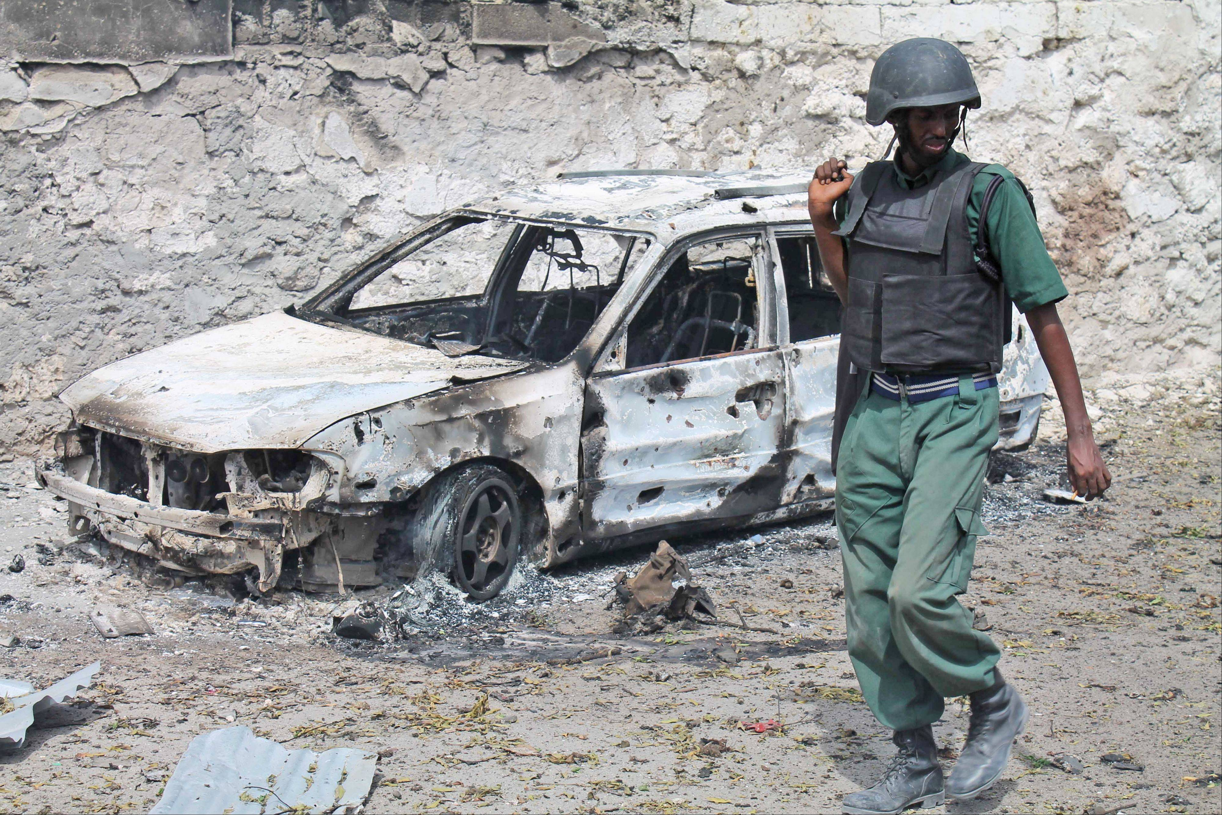 A Somali soldier walks near a destroyed car near the entrance of Mogadishu's court complex in Somalia, Sunday. Militants launched a serious and sustained assault on Mogadishu's main court complex Sunday, detonating at least two blasts, taking an unknown number of hostages and exchanging extended volleys of gunfire with government security forces, witnesses said.