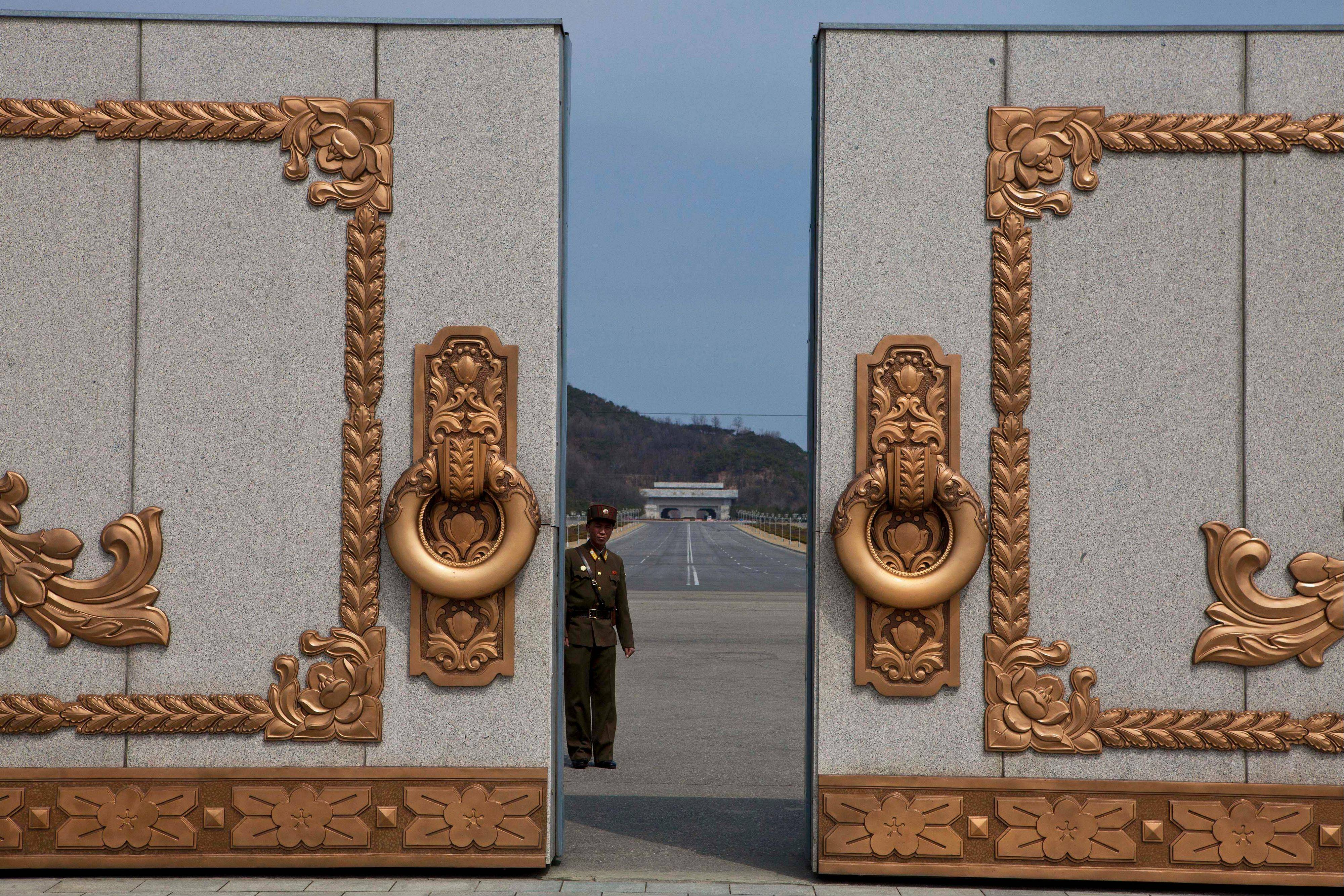 A North Korean soldier guarding the entrance to Pyongyang's Kumsusan mausoleum, where the bodies of the late leaders Kim Il Sung and Kim Jong Il lie embalmed, looks back through the doors of the main gate Monday. North Koreans turned out on Monday to mark the 101st birthday of Kim Il Sung.