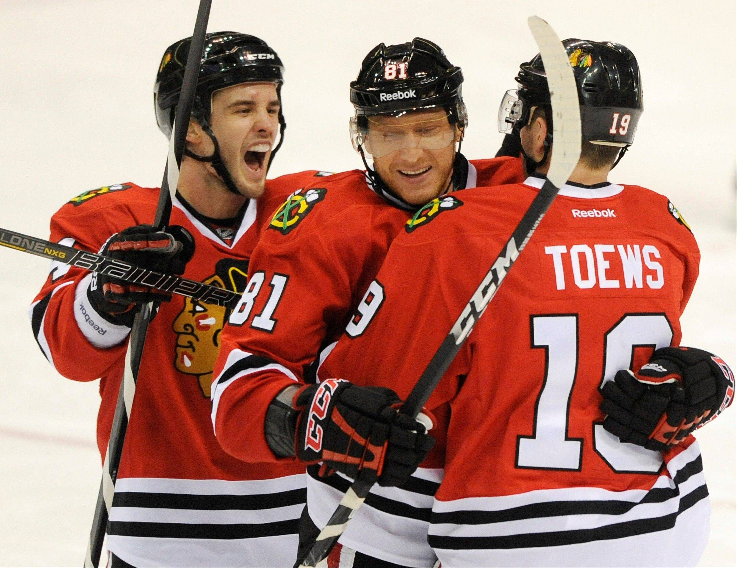 Blackhawks forward Marian Hossa celebrates his goal Sunday against the St. Louis Blues with Jonathan Toews and Niklas Hjalmarsson in the third period at United Center.