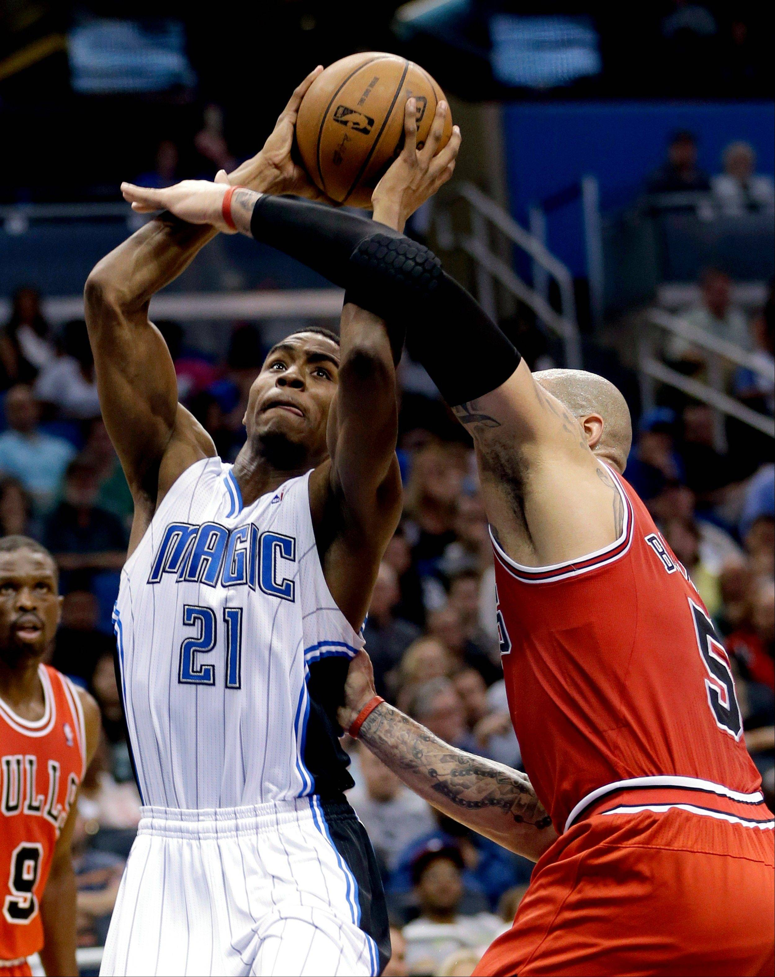 Orlando Magic's Maurice Harkless (21) shoots over the Bulls' Carlos Boozer, right, during the second half of the basketball game Monday in Orlando. The Bulls won 102-84.