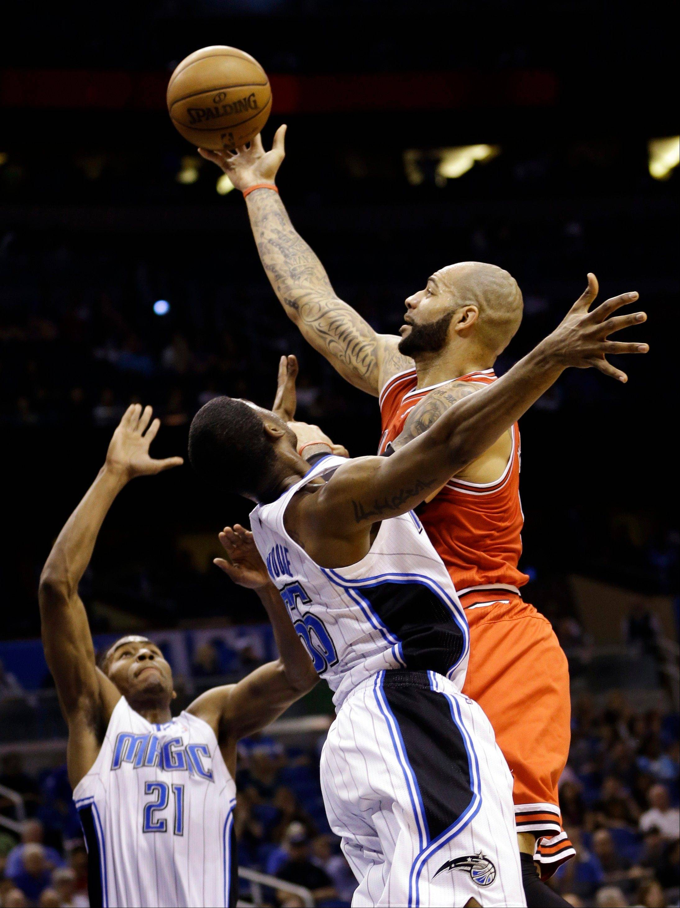 The Bulls' Carlos Boozer, right, shoots over Orlando Magic's Maurice Harkless (21) and E'Twaun Moore during the first half of the game Monday in Orlando.