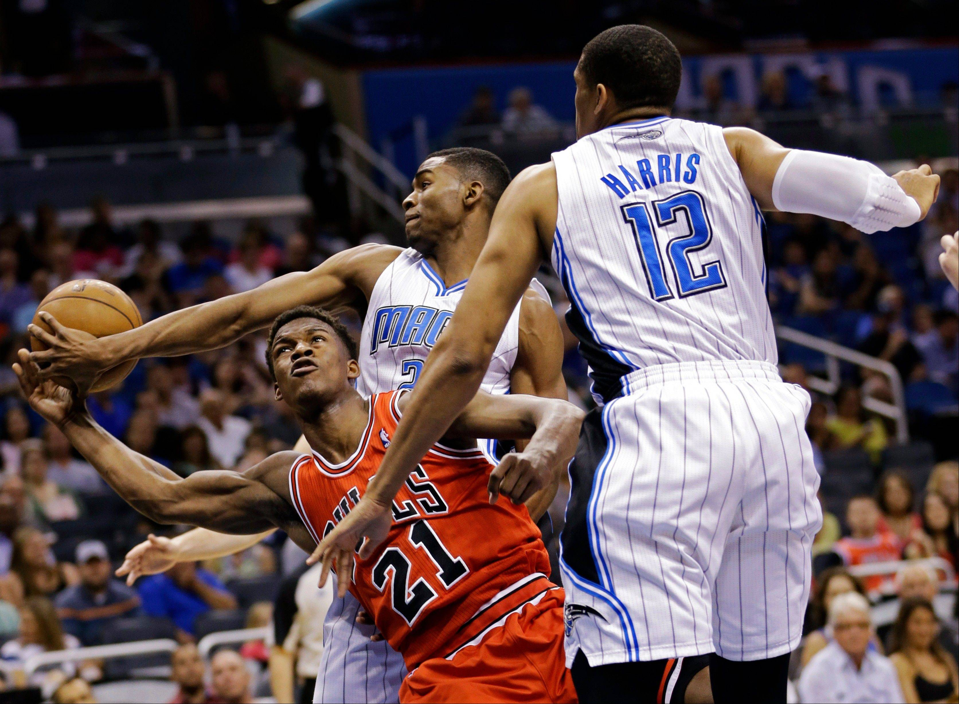 The Bulls' Jimmy Butler (21) loses the ball under pressure from Orlando Magic's Maurice Harkless, center, and Tobias Harris (12) during the first half of the game Monday in Orlando.