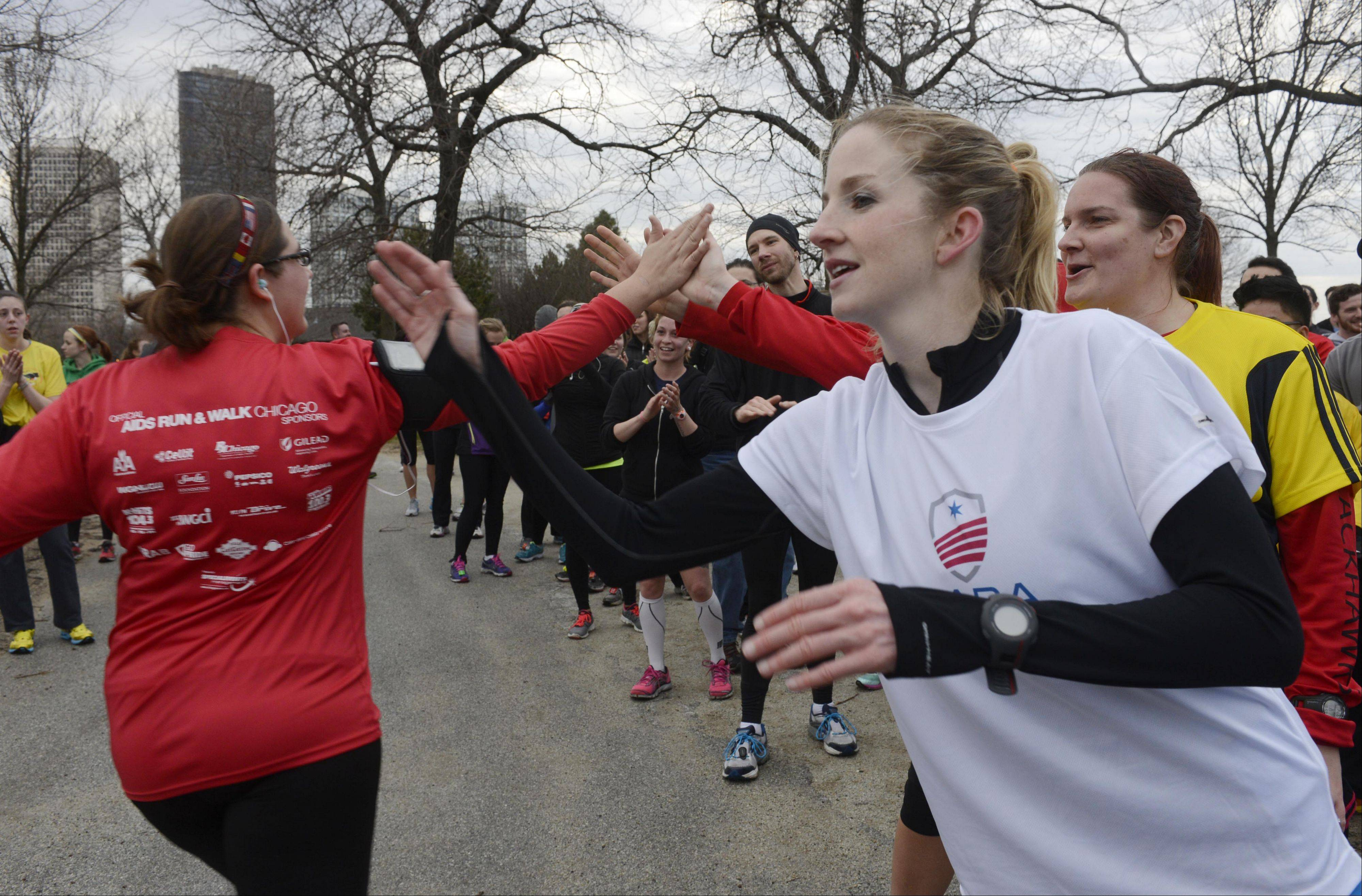 Meg Sullivan, training program manager of the Chicago Area Runners Association, high-fives participants at the end of a memorial run from Foster Avenue Beach in Chicago, honoring victims of the Boston Marathon bombing.
