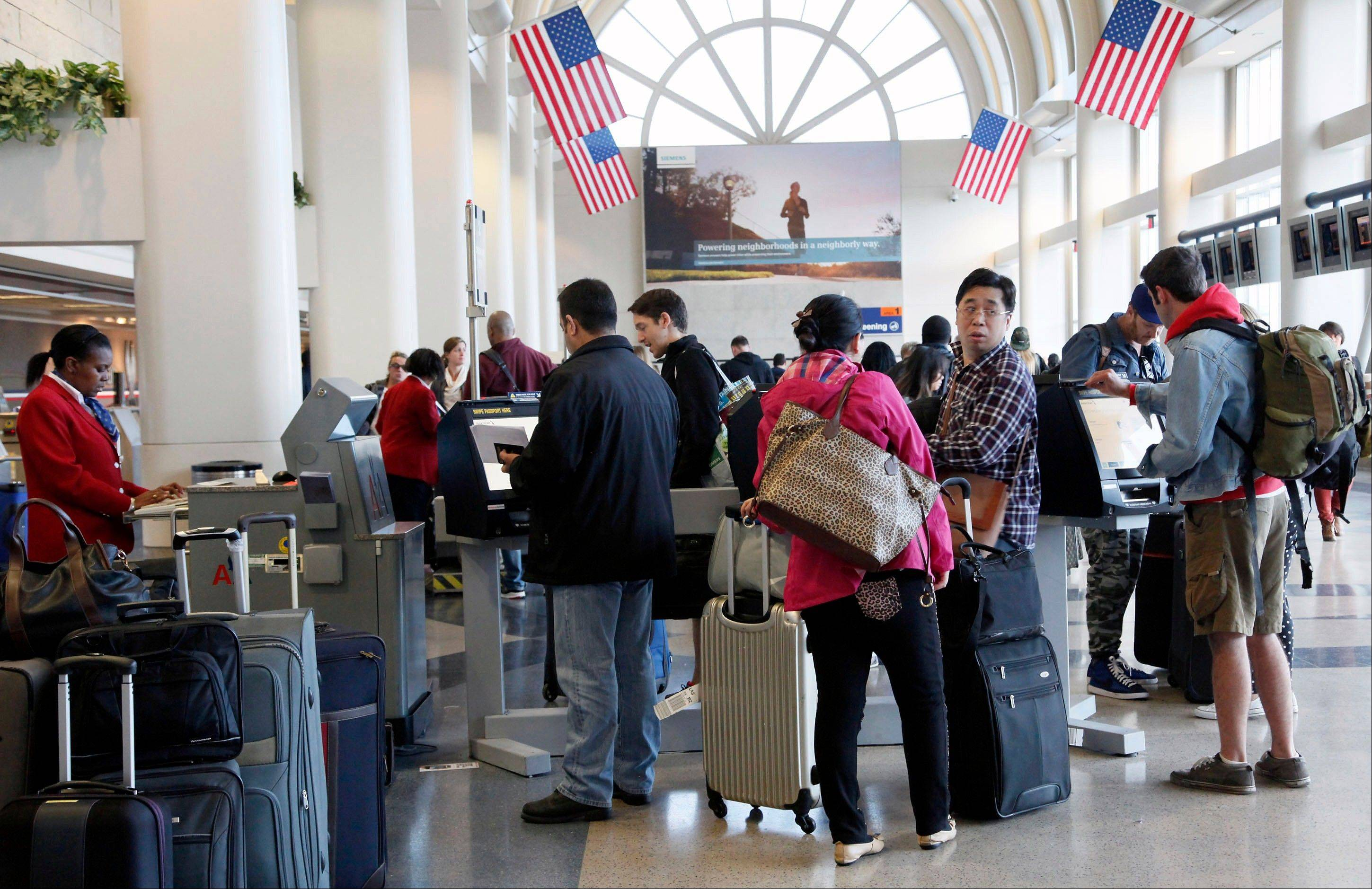 Passengers at the American Airlines counter wait Tuesday to check in to their flights at Los Angeles International Airport. Computer problems forced American Airlines to ground flights across the country Tuesday after the airline was unable to check passengers in and book passengers.