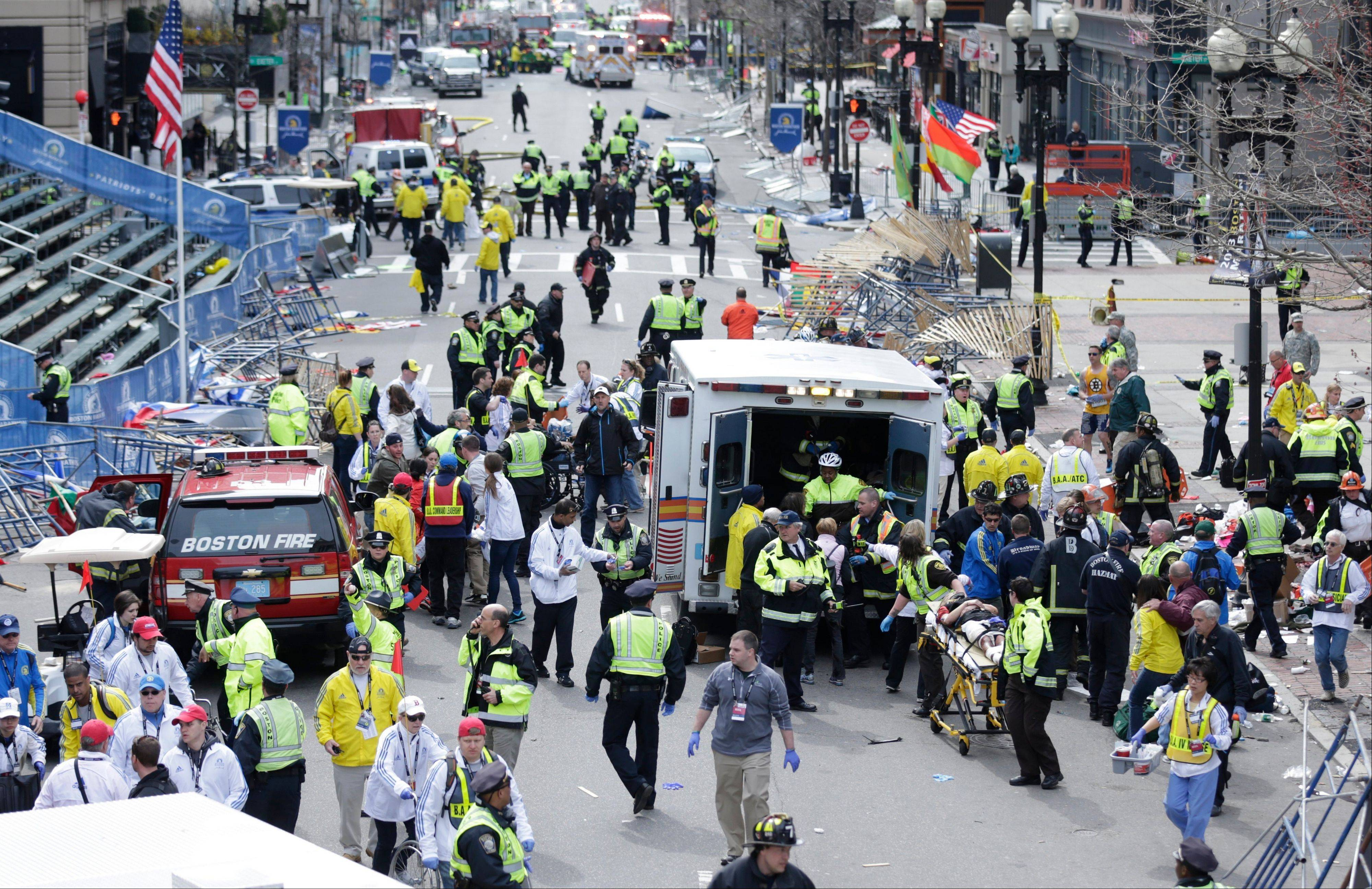 Medical workers help injured people at the finish line of the 2013 Boston Marathon after the explosions in Boston yesterday.
