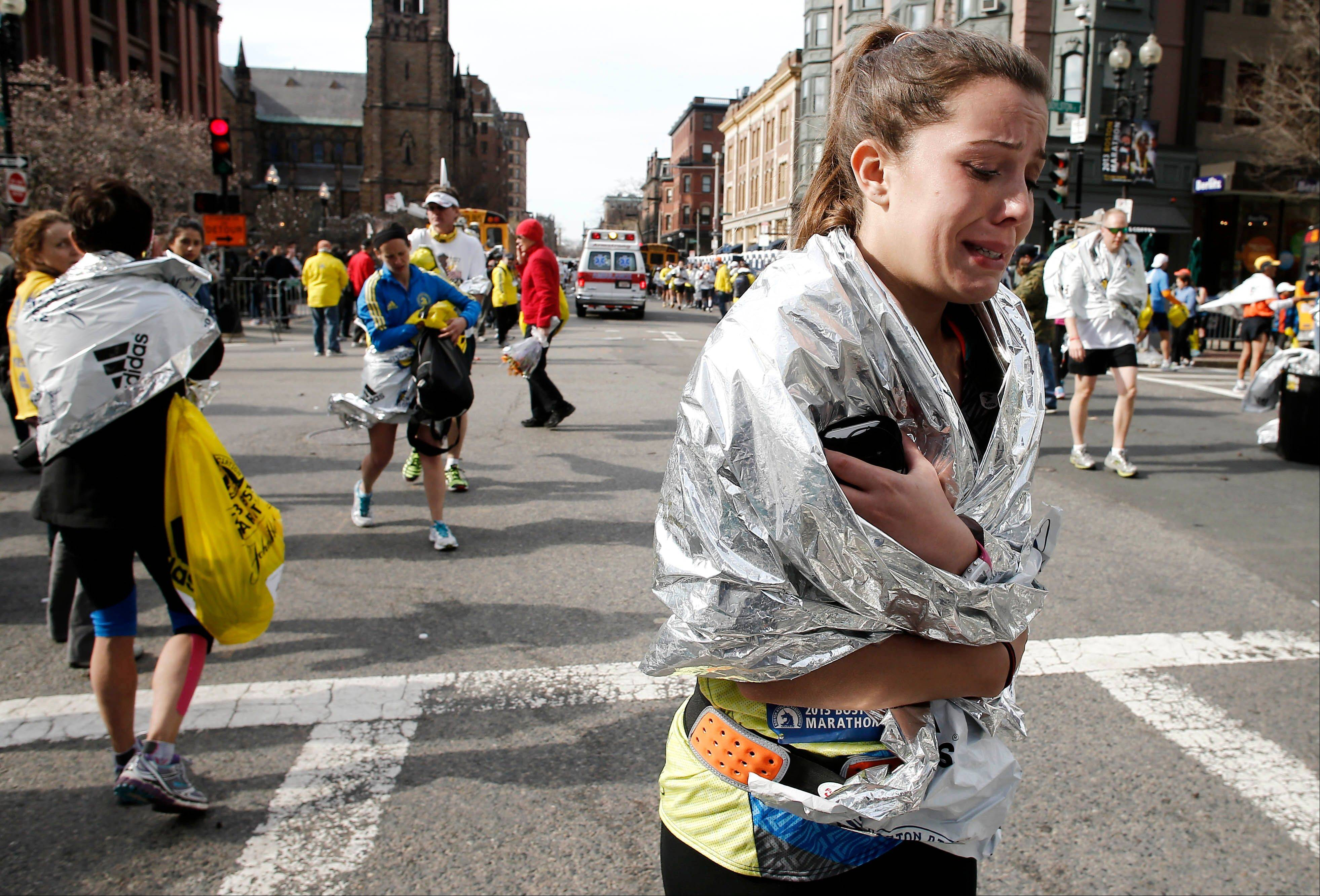 An unidentified Boston Marathon runner leaves the course near Copley Square after the explosions in Boston on Monday.